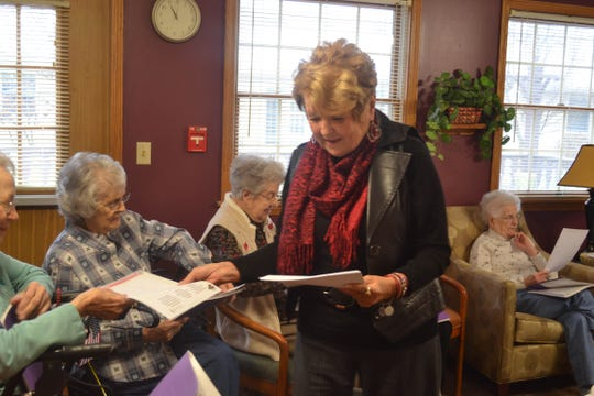 "Barb Engler-Moran gives members of the Bible study copies of ""The Legend of the Candy Cane"" so they can share the spiritual story with friends."