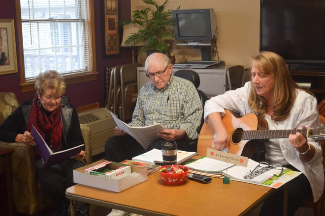 Barb Engler-Moran, George Gibson, and Donna Miller sing during a Bible study at Bethany Place. Miller brings her guitar to the studies to sing for, and with, the residents.