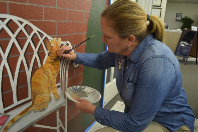 Muralist Beth Sage works on a cat in a new mural she is painting at Rutherford House in Fremont.