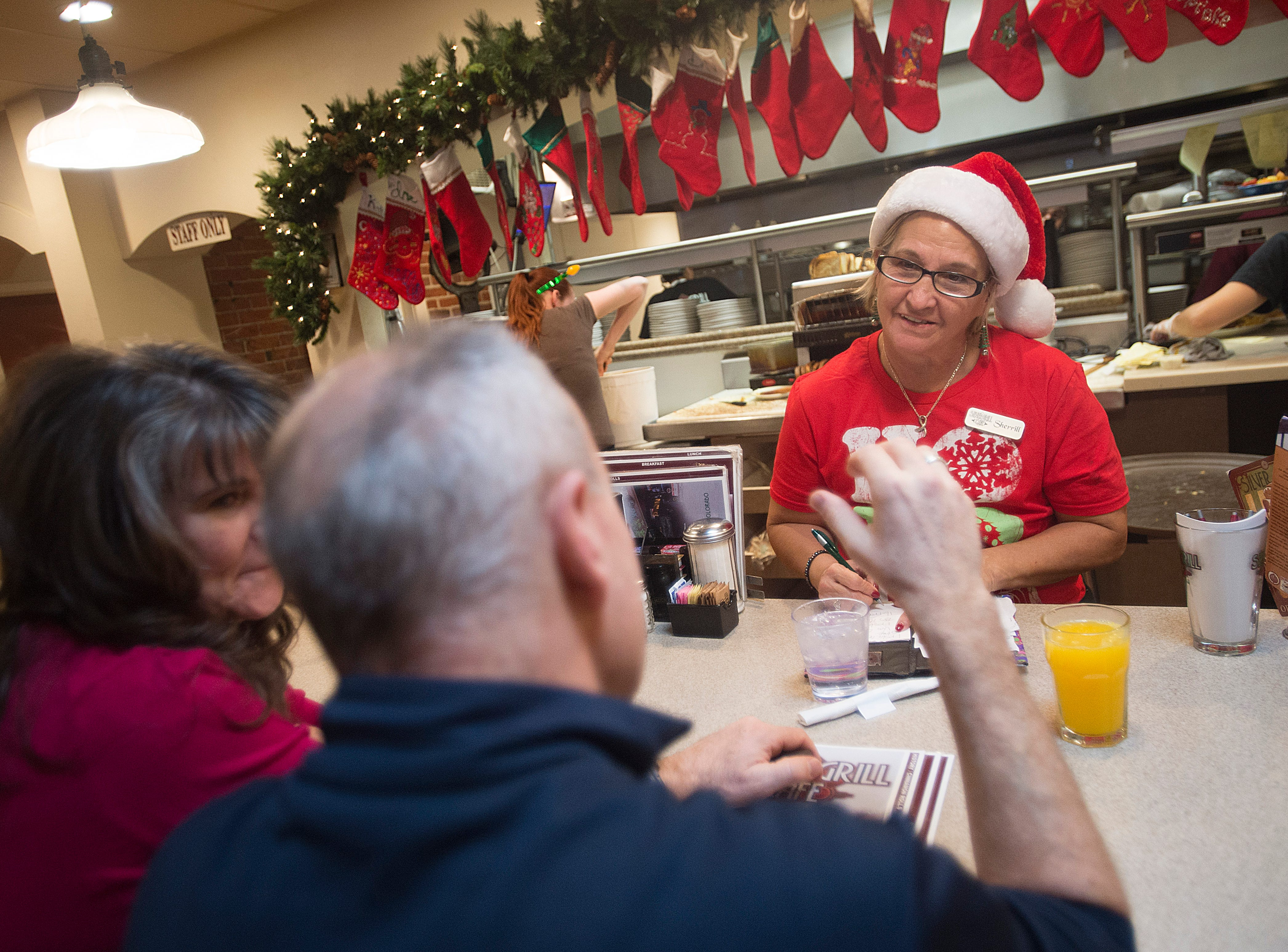 Sherrill Lewis wears a Santa hat as she takes a brunch order behind the counter at Silver Grill Cafe in Old Town on Monday, December 24, 2018.