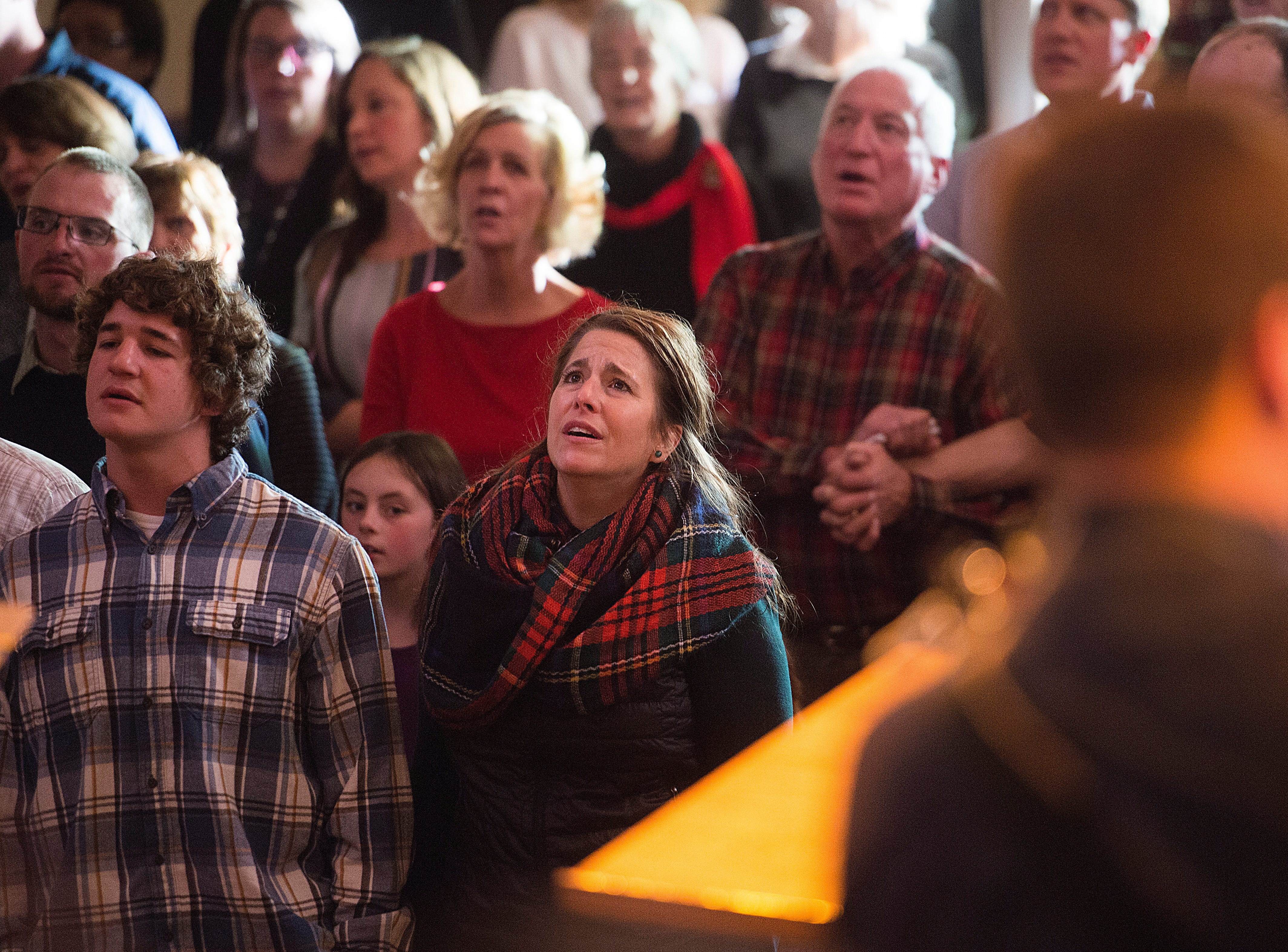 People sing along to Christmas hymns during a candlelight service at Mountain View Community Church on Monday, December 24, 2018.