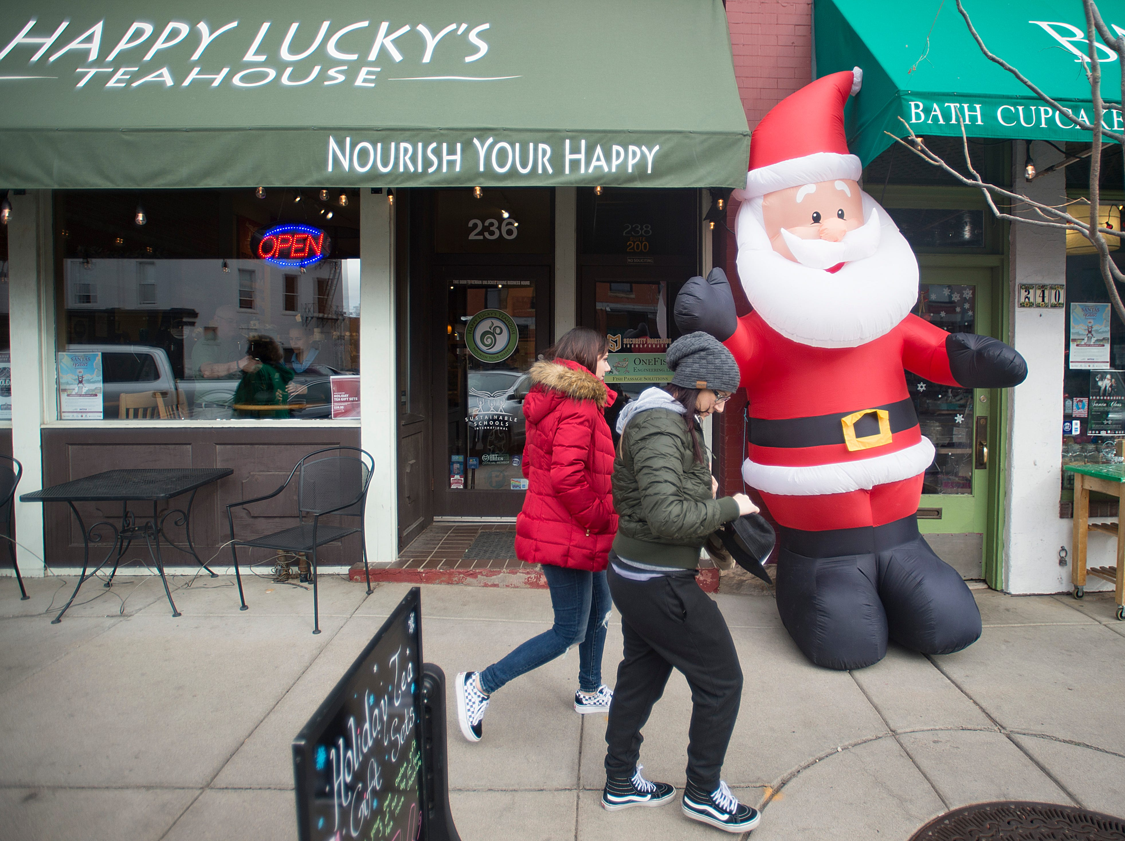 People walk past decorations in Old Town on Monday, December 24, 2018.