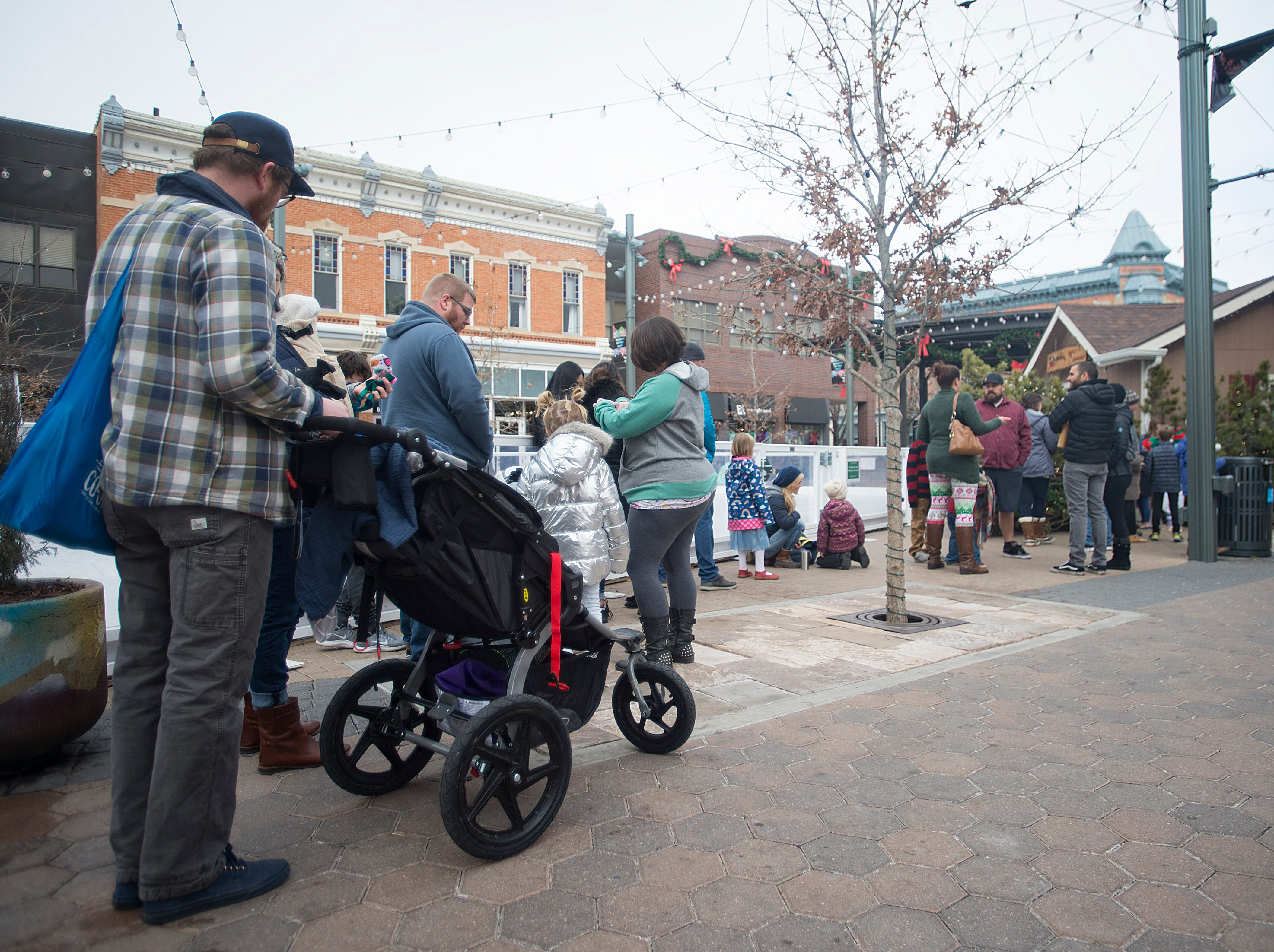 People line up to visit Santa Claus in Old Town Square on Monday, December 24, 2018.