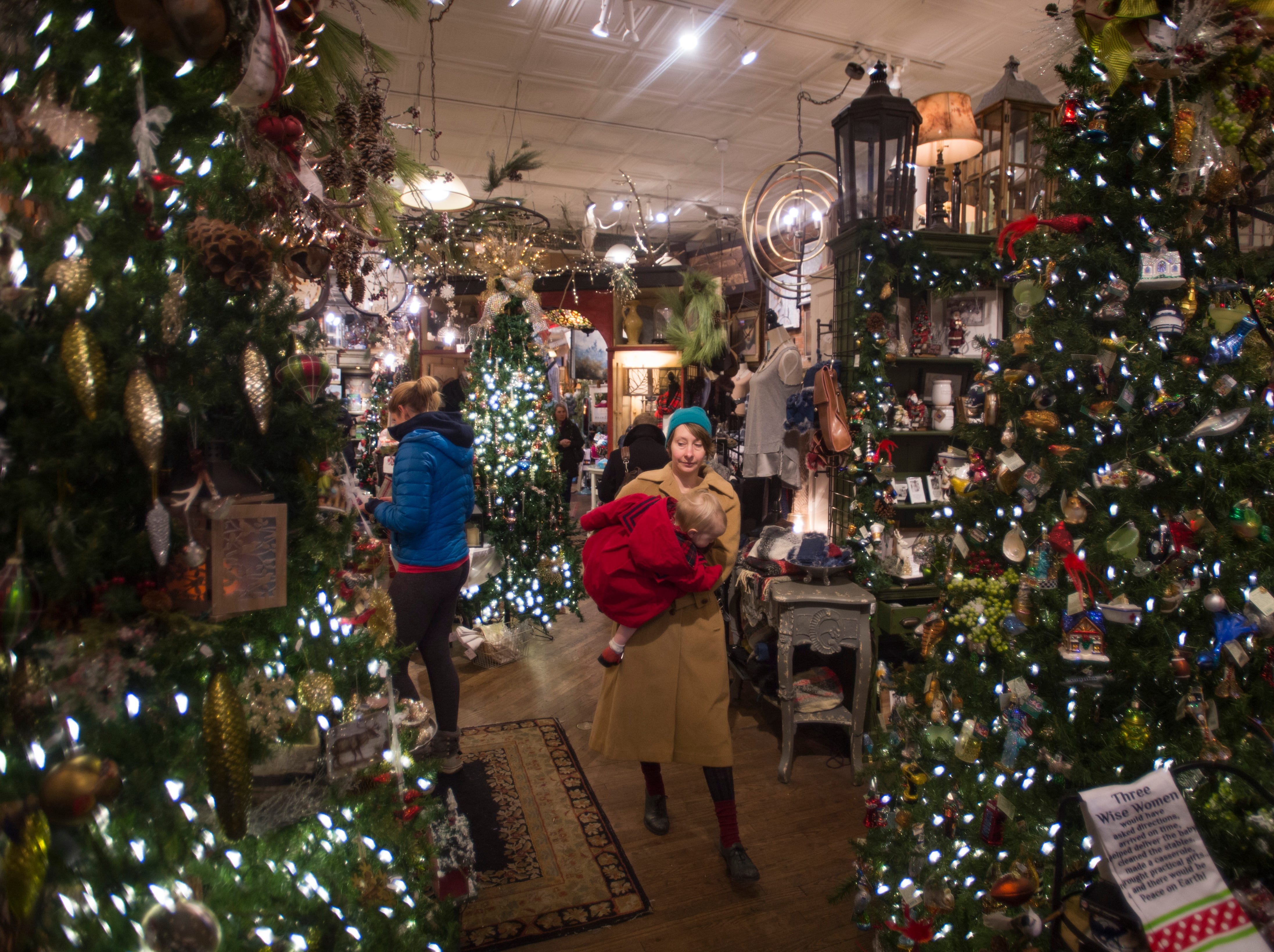 Natalie Scarlett carries her daughter, Imogen Williams, through holiday displays as they try to get some last minute shopping in at The Perennial Gardener in Old Town on Monday, December 24, 2018.