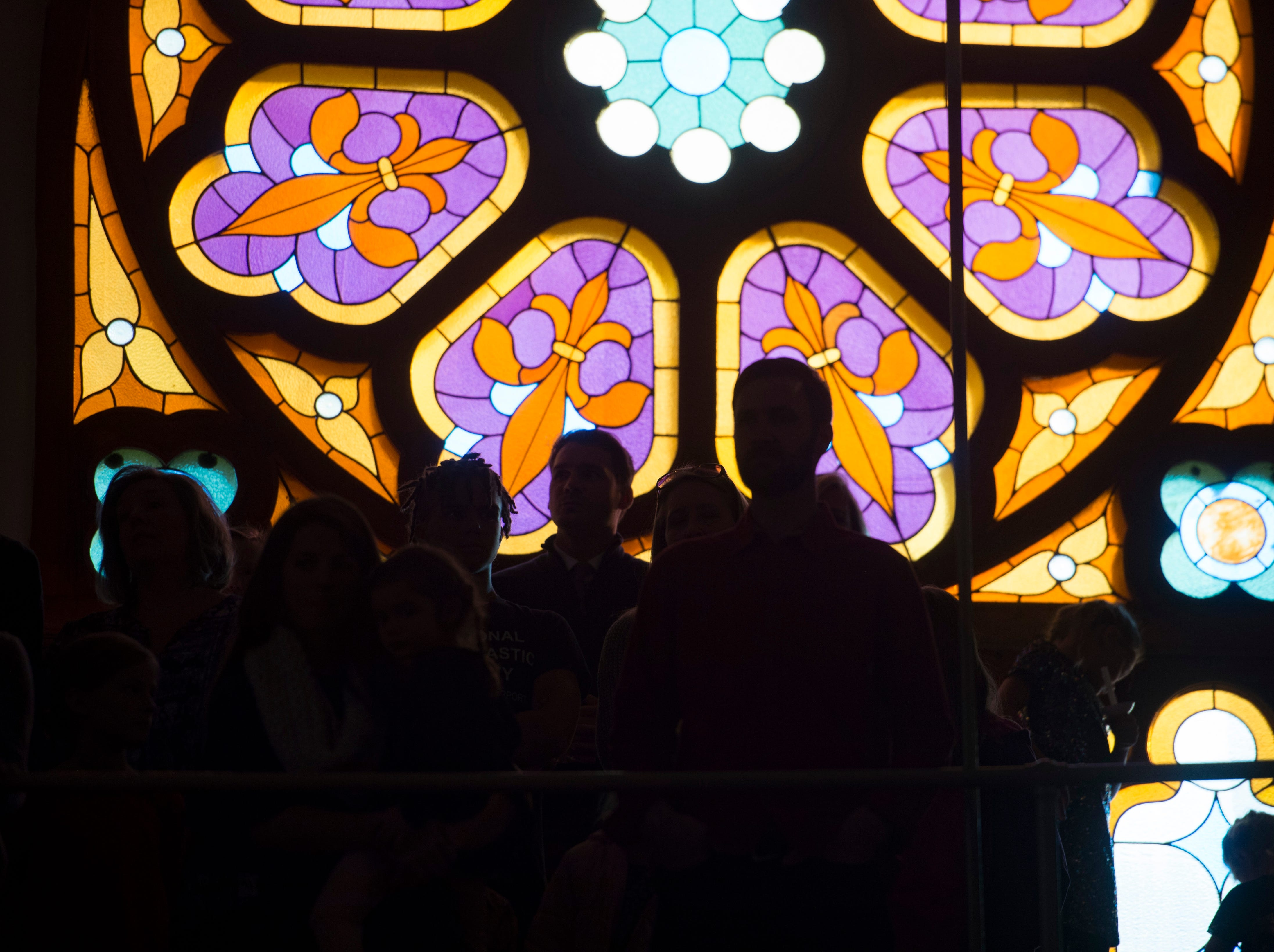 People are silhouetted against stained glass during a candlelight service at Mountain View Community Church on Monday, December 24, 2018.