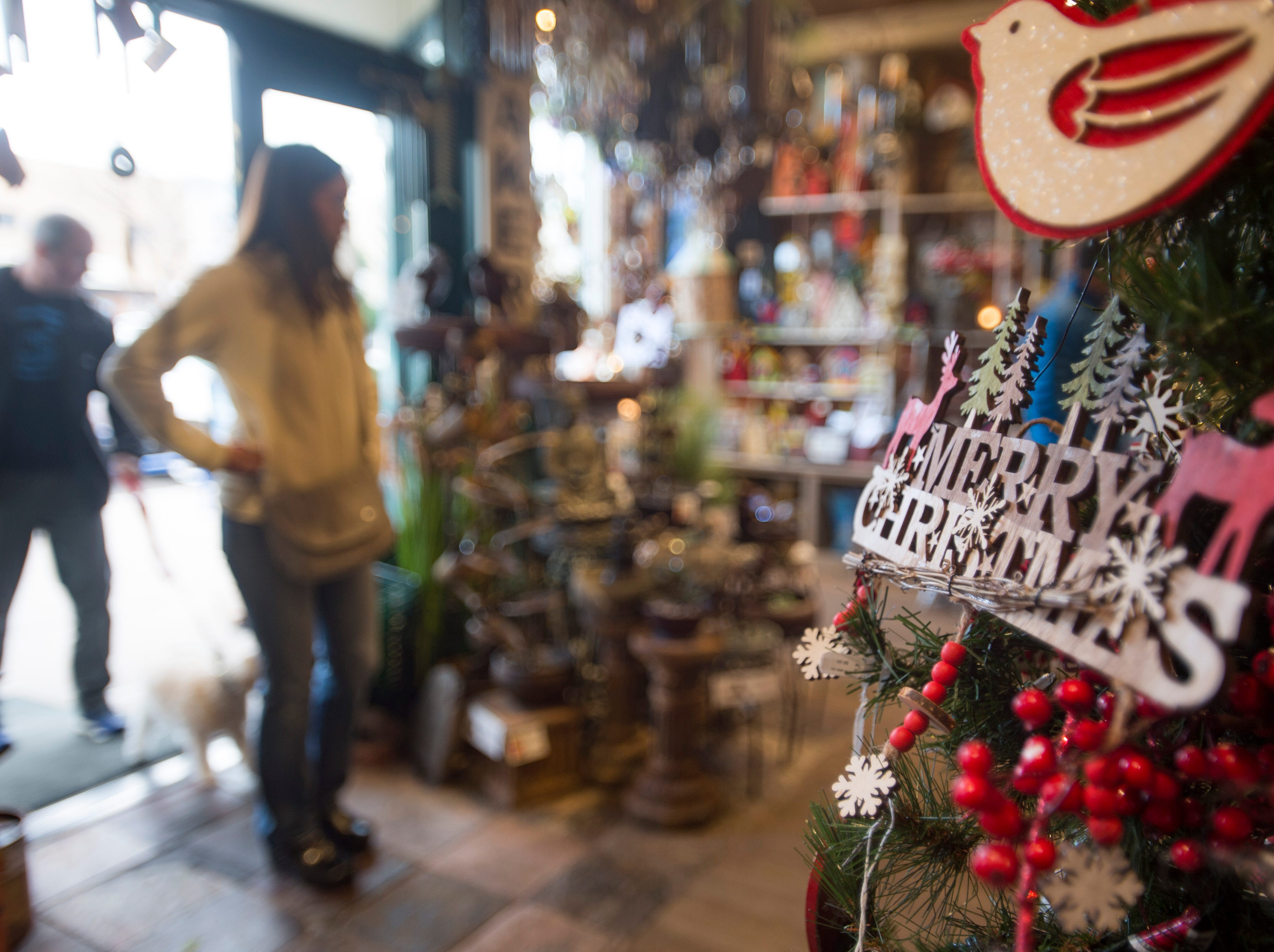 People walk into The Perennial Gardener for last-minute holiday shopping in Old Town on Monday, December 24, 2018.