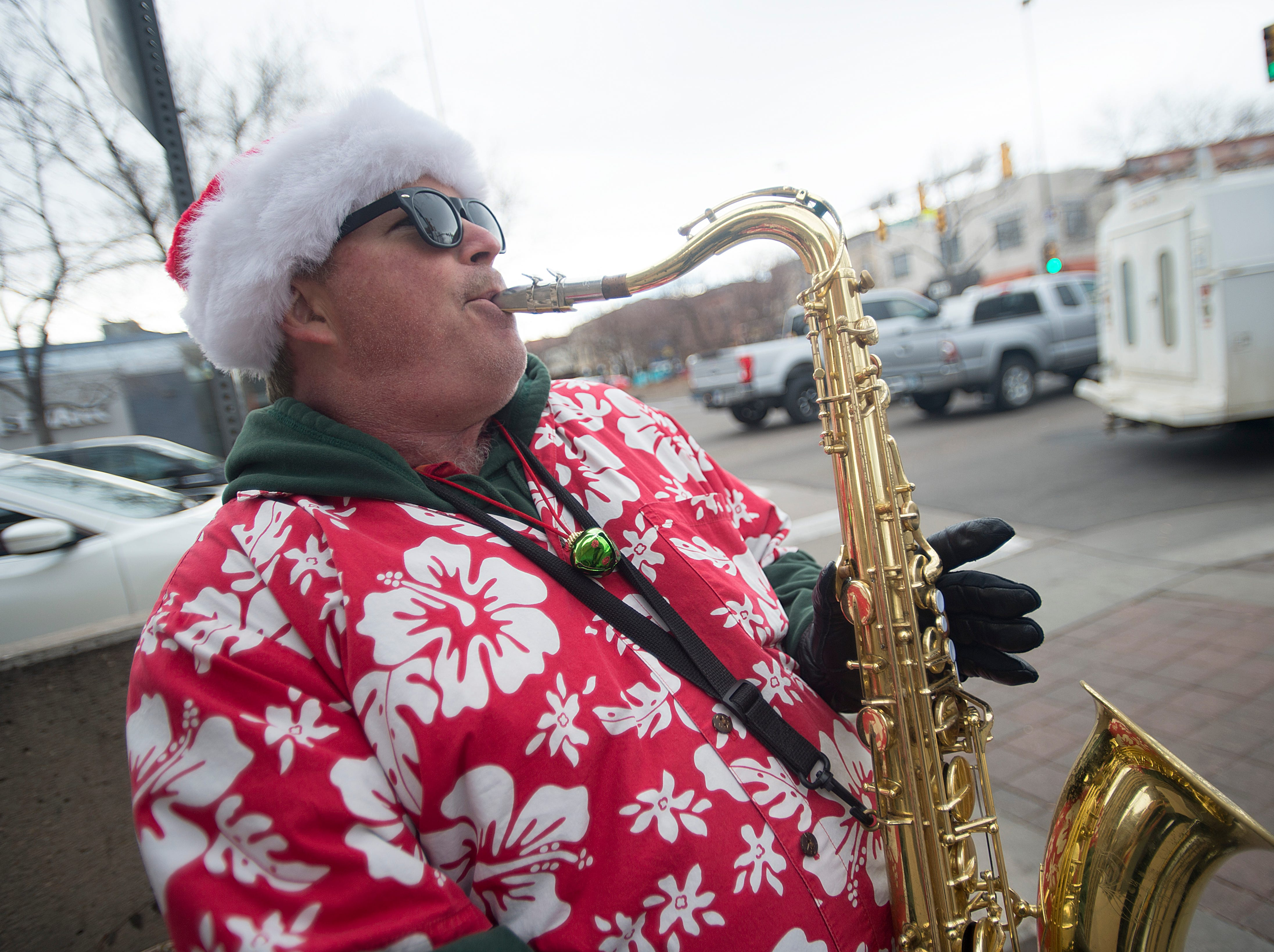 Michael Brown performs Christmas tunes on his saxophone for tips in Old Town on Monday, December 24, 2018.