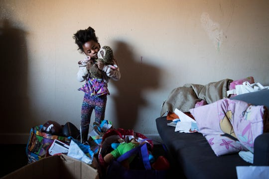 Tyanna Hunter, 5, grabs one of her favorite toys out of a box before her family leaves their room at the Economy Inn on Thursday, January 25, 2018. The motel was condemned and residents were given less than 24 hours to pack up, leave, and find a new place to go.