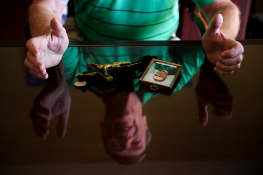 Jim Graham is reflected off his glass top desk, where a photograph of Rev. Thomas Sullivan and his crucifix rest, on Tuesday, July 18, 2018. Graham has spent years investigating his relation to Sullivan, who he believes to be his biological father.