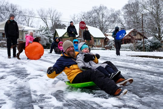 Chris Haddon and his two-year-old son Augustus sled down Townes Street in the North Main neighborhood on Wednesday, Jan. 17, 2018.