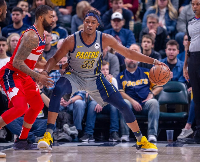 Indiana Pacers center Myles Turner (33) works the ball toward the basket against the defense of Washington Wizards forward Markieff Morris (5) during an NBA basketball game, Sunday, Dec. 23, 2018, in Indianapolis.