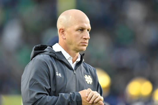 Fighting Irish defensive coordinator Clark Lea watches warmups before the game against the Stanford Cardinal at Notre Dame Stadium.