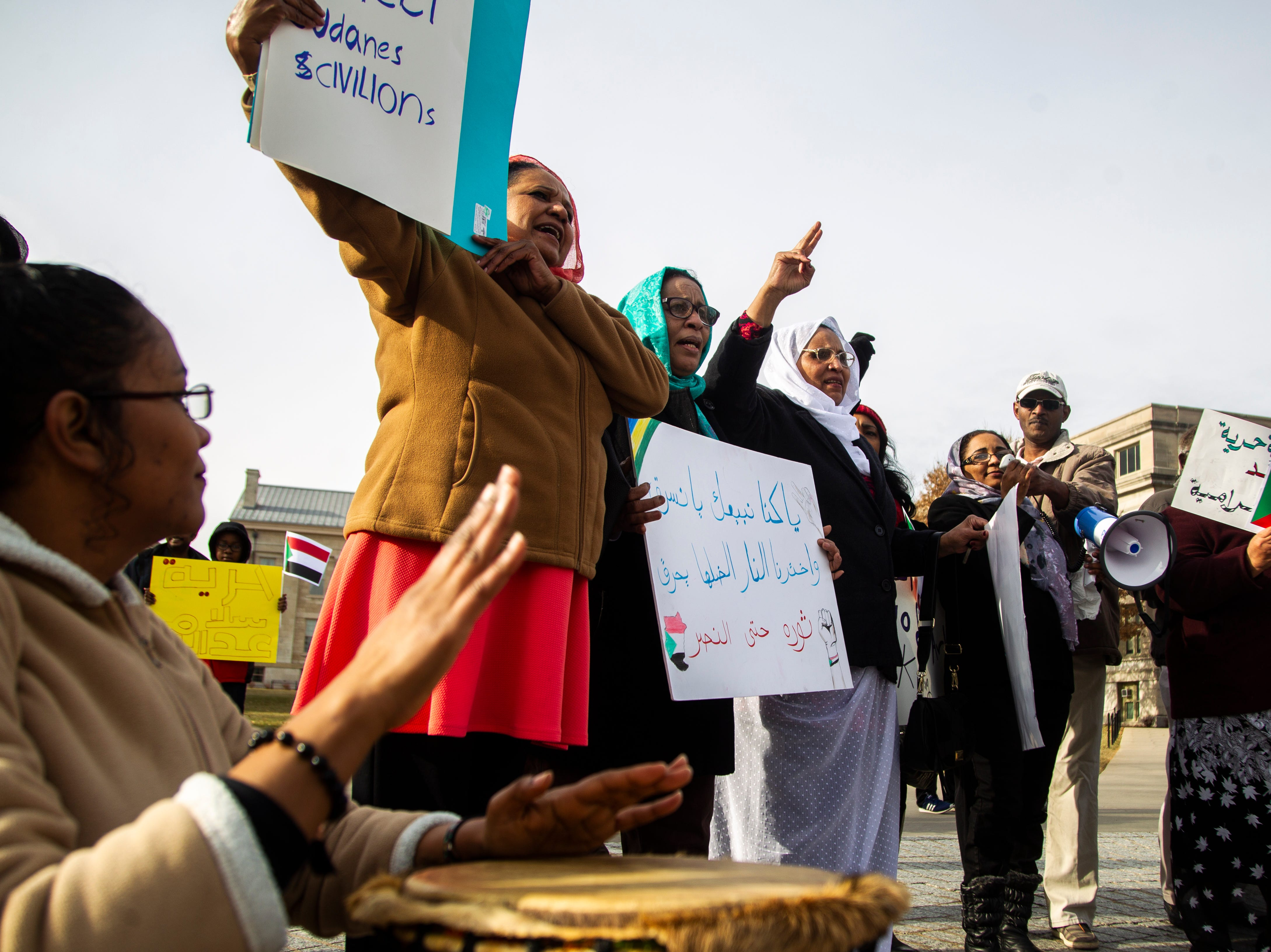 Rania Selimau beats on a drum while Sudanese members of the Iowa City community chant during a peaceful protest in opposition to the killings in Sudan on Monday, Dec. 24, 2018, in downtown Iowa City. They chanted in Arabic about their opposition to Sudanese President Omar al-Bashir.