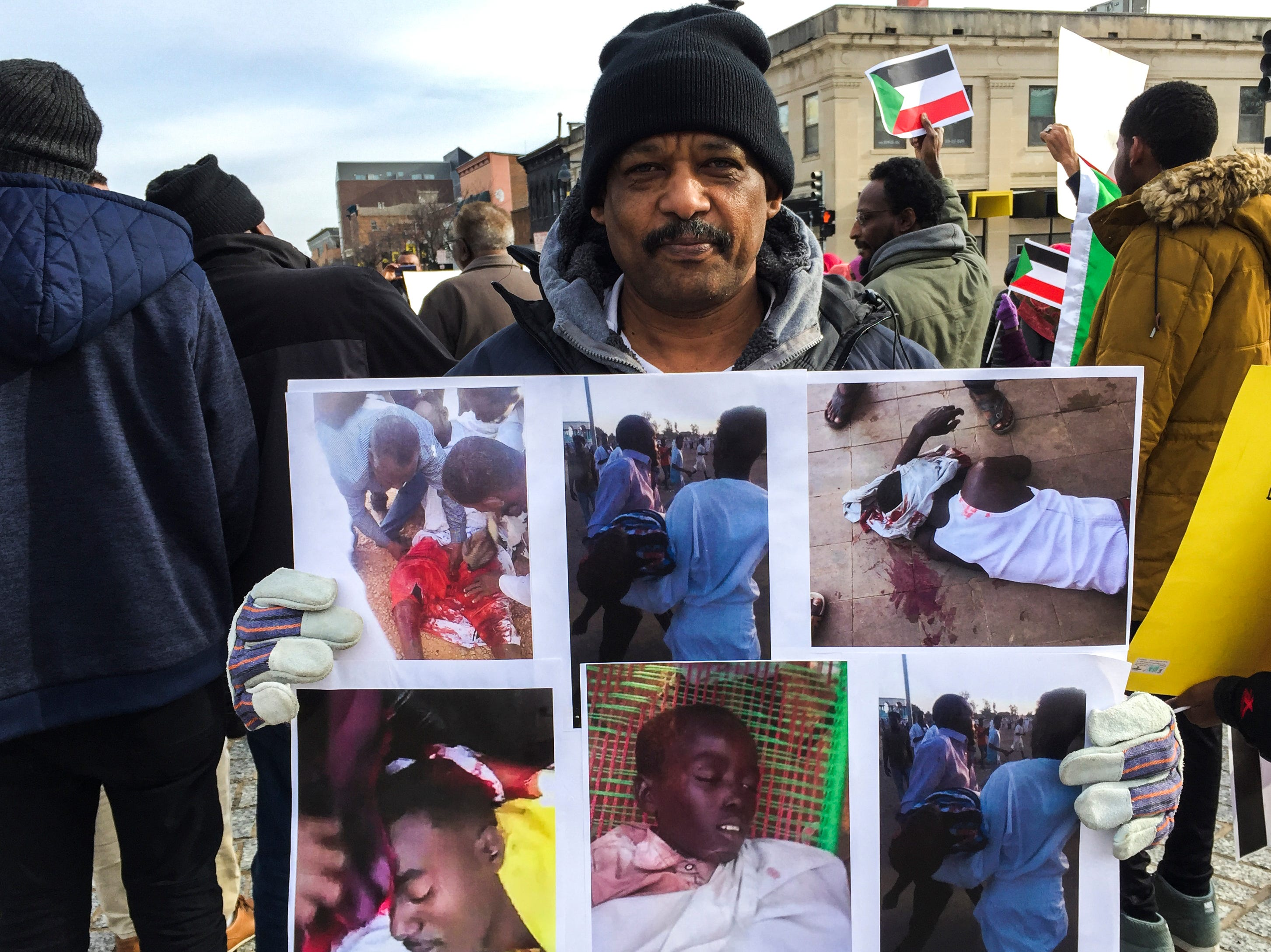 Fakhreldein Hasaballah holds a poster with images of murdered protesters in Sudan while Sudanese members of the Iowa City community gather during a peaceful protest in opposition to the killings in their home country on Monday, Dec. 24, 2018, in downtown Iowa City. Hasaballah has lived in Iowa for two years after waiting to receive a visa from a lottery pool for two years.
