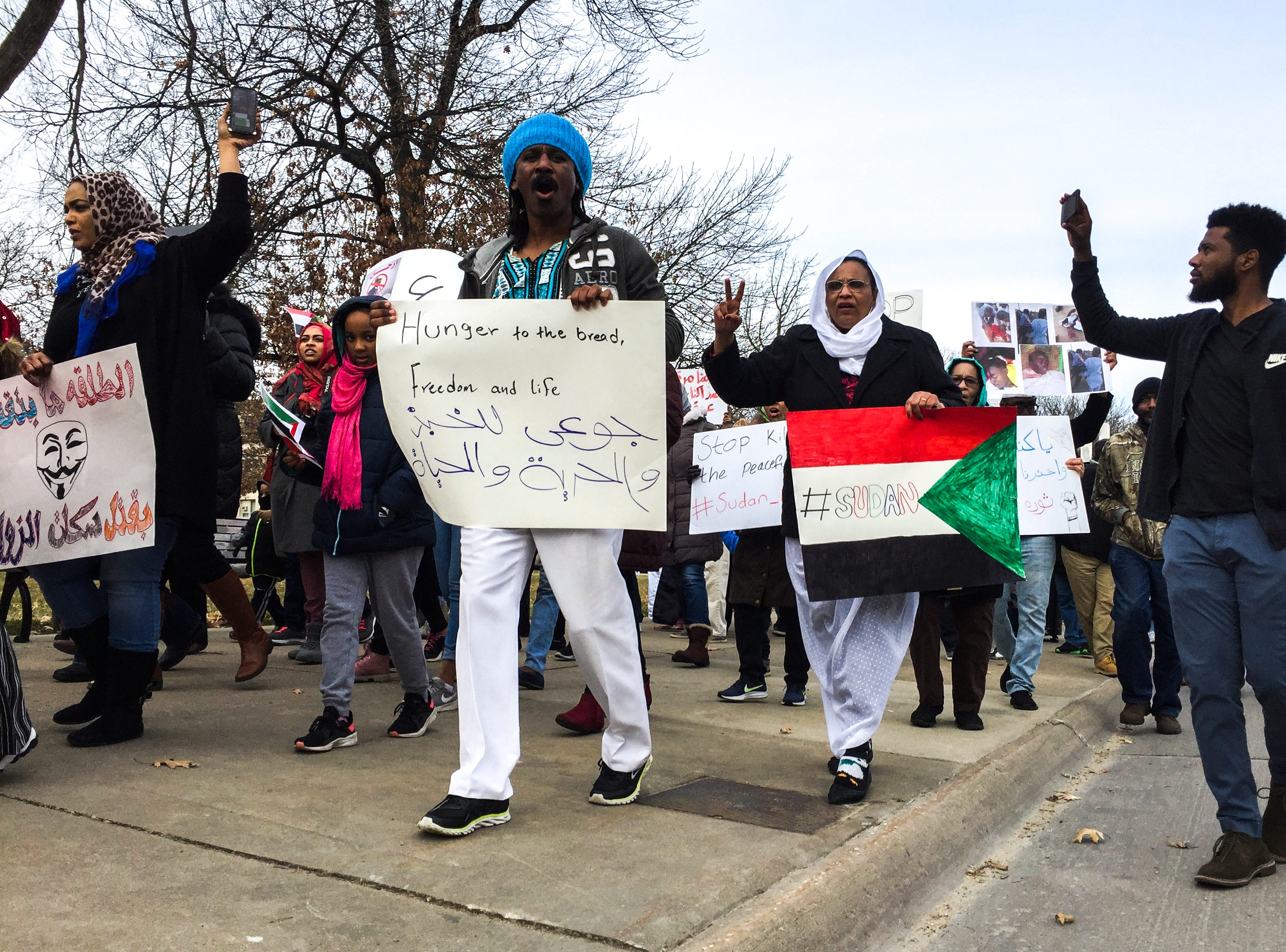 "Sudanese members of the Iowa City community march during a peaceful protest in opposition to the killings in their home country on Monday, Dec. 24, 2018, in downtown Iowa City. They chanted lyrics from the song, ""Get up, Stand up."""