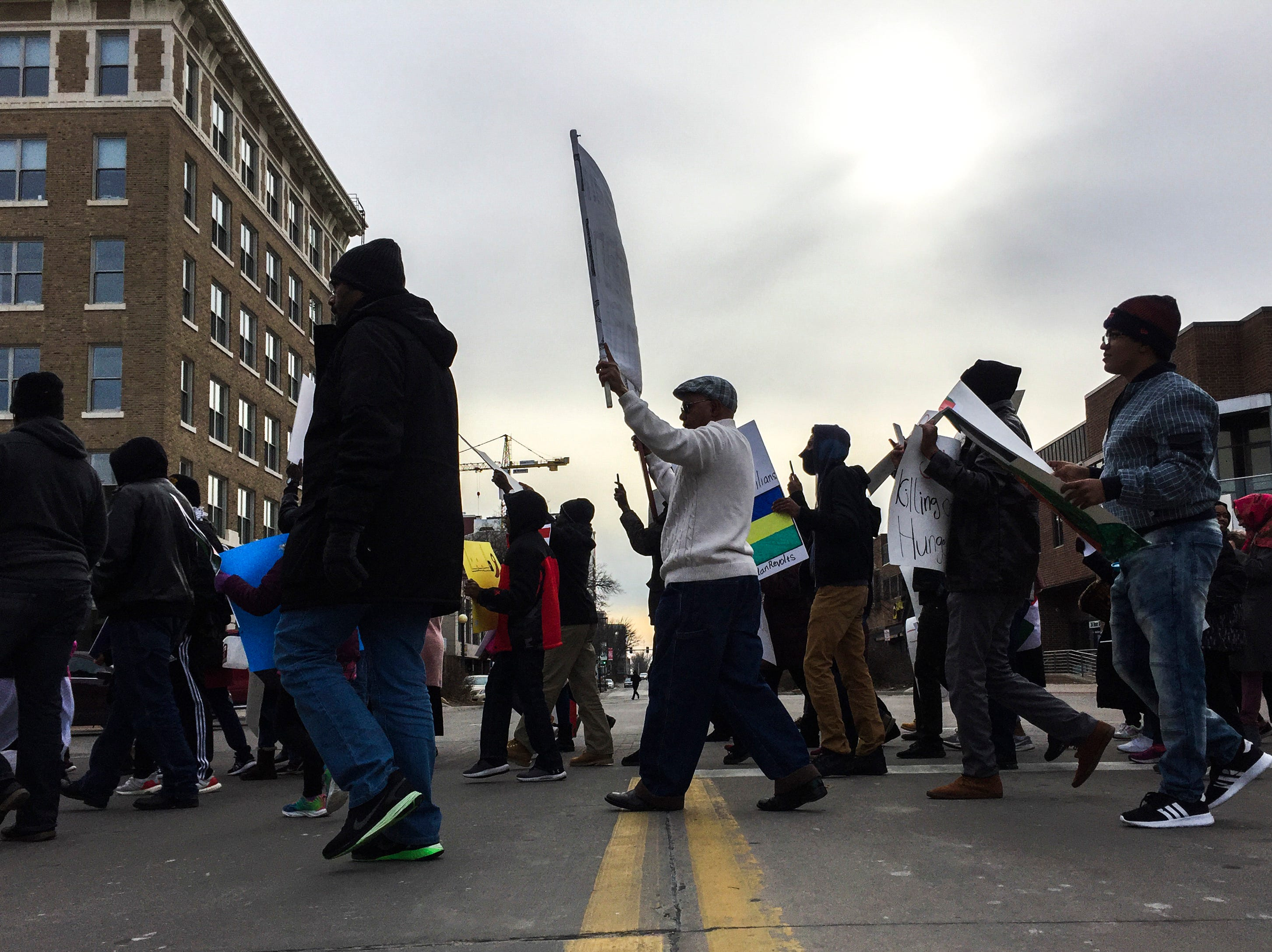 Sudanese members of the Iowa City community march during a peaceful protest in opposition to the killings in their home country on Monday, Dec. 24, 2018, in downtown Iowa City.
