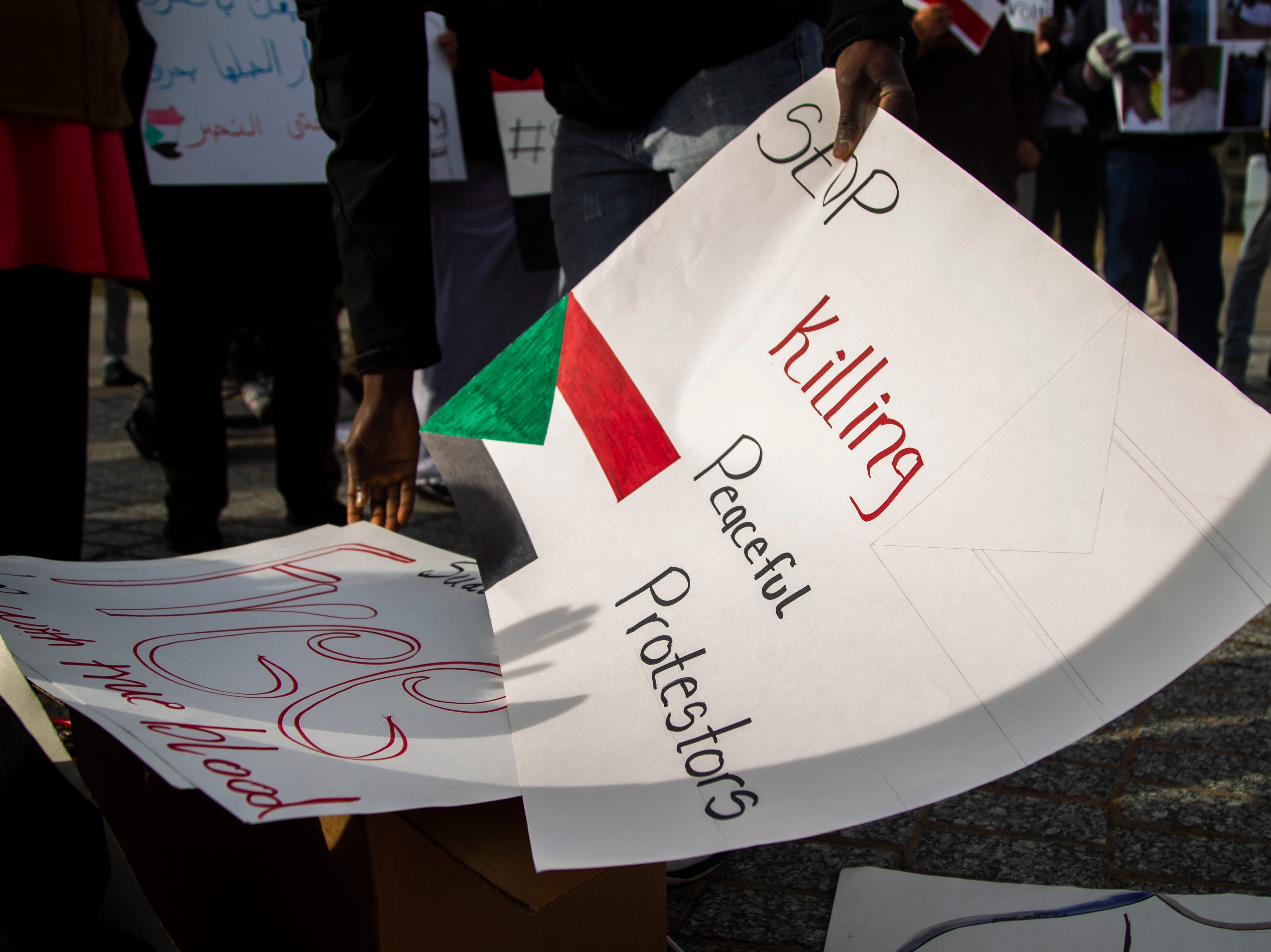 Sudanese members of the Iowa City community gather during a peaceful protest in opposition to the killings in Sudan on Monday, Dec. 24, 2018, in downtown Iowa City.