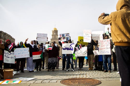 Sudanese members of the Iowa City community gather during a peaceful protest in opposition to the killings in their home country on Monday, Dec. 24, 2018, along Clinton Street in front of the Old Capitol Building on the Pentacrest in downtown Iowa City.