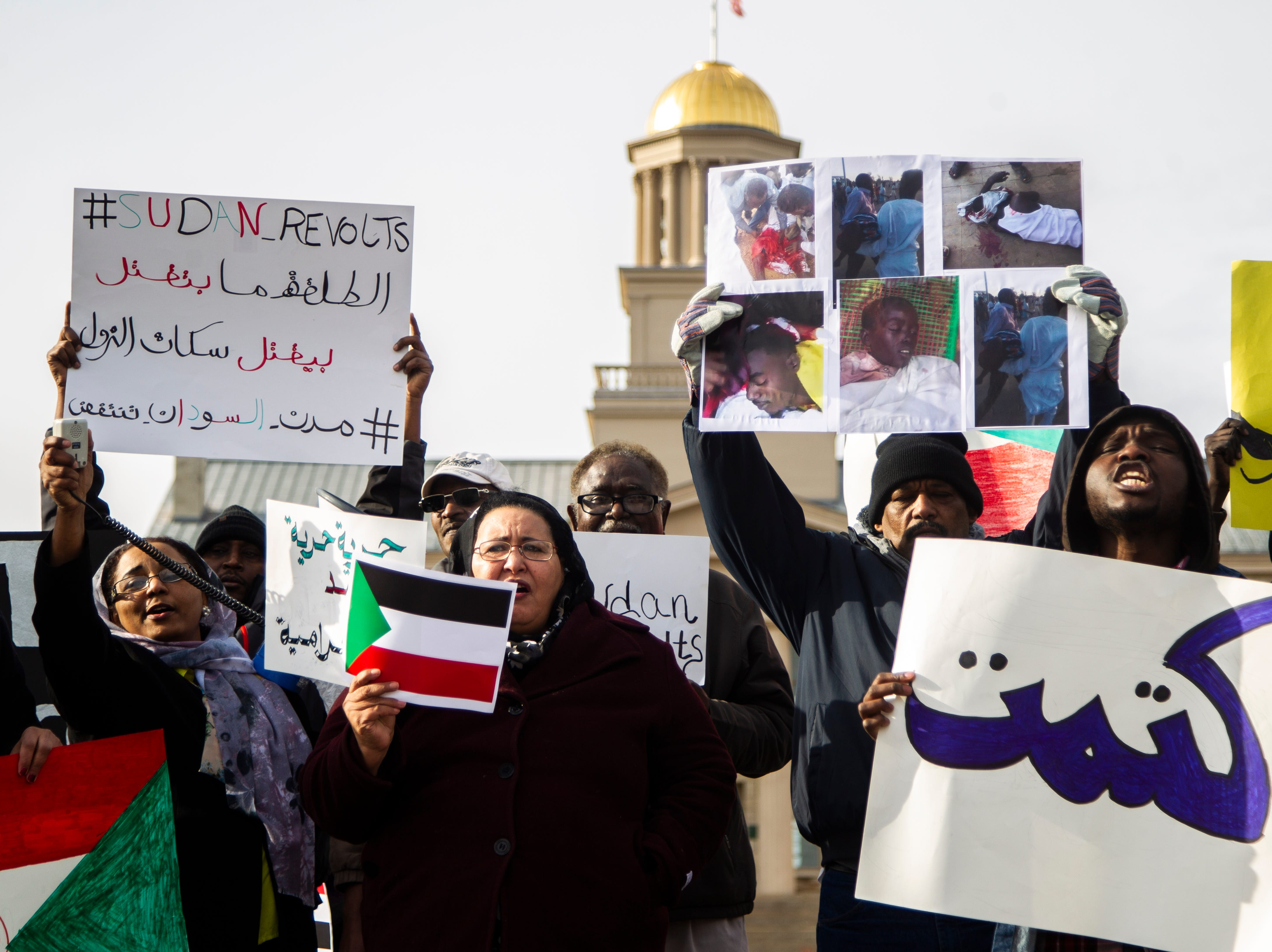 Sudanese refugee Omer Idres, right, chants with members of the Iowa City community gather during a peaceful protest in opposition to the killings in their home country on Monday, Dec. 24, 2018, along Clinton Street in front of the Old Capitol Building on the Pentacrest in downtown Iowa City. Idres came to the United States five years ago after waiting two years before being selected in a visa lottery.