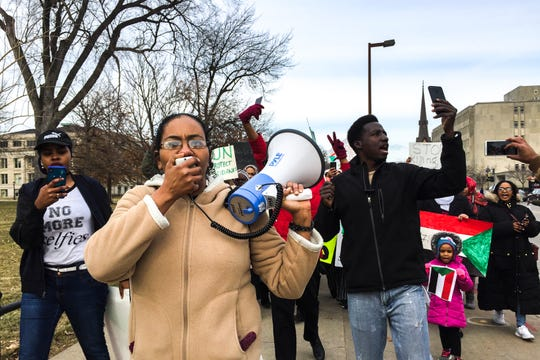 Rania Selimau leads a chant while marching with Sudanese members of the Iowa City community during a peaceful protest in opposition to the killings in their home country on Monday, Dec. 24, 2018, in downtown Iowa City.
