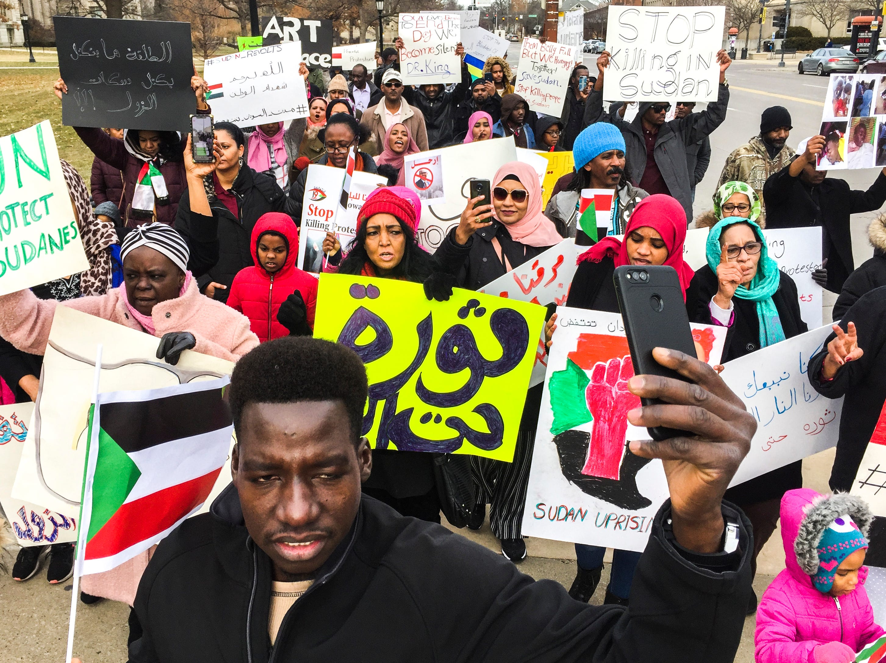 Sudanese refugee Aziz Ali, 28, records a livestream while he marches with members of the Iowa City community during a peaceful protest in opposition to the killings in Sudan on Monday, Dec. 24, 2018, in downtown Iowa City.