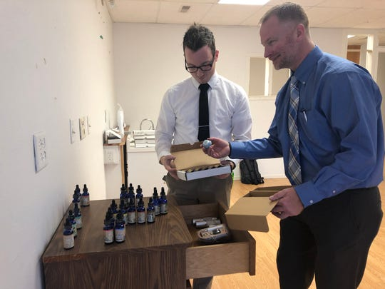 Joe Scholz and Kevin Threlkeld set up Your CBD Store in Iowa City hemp oil products Thursday, Dec. 20, 2018.