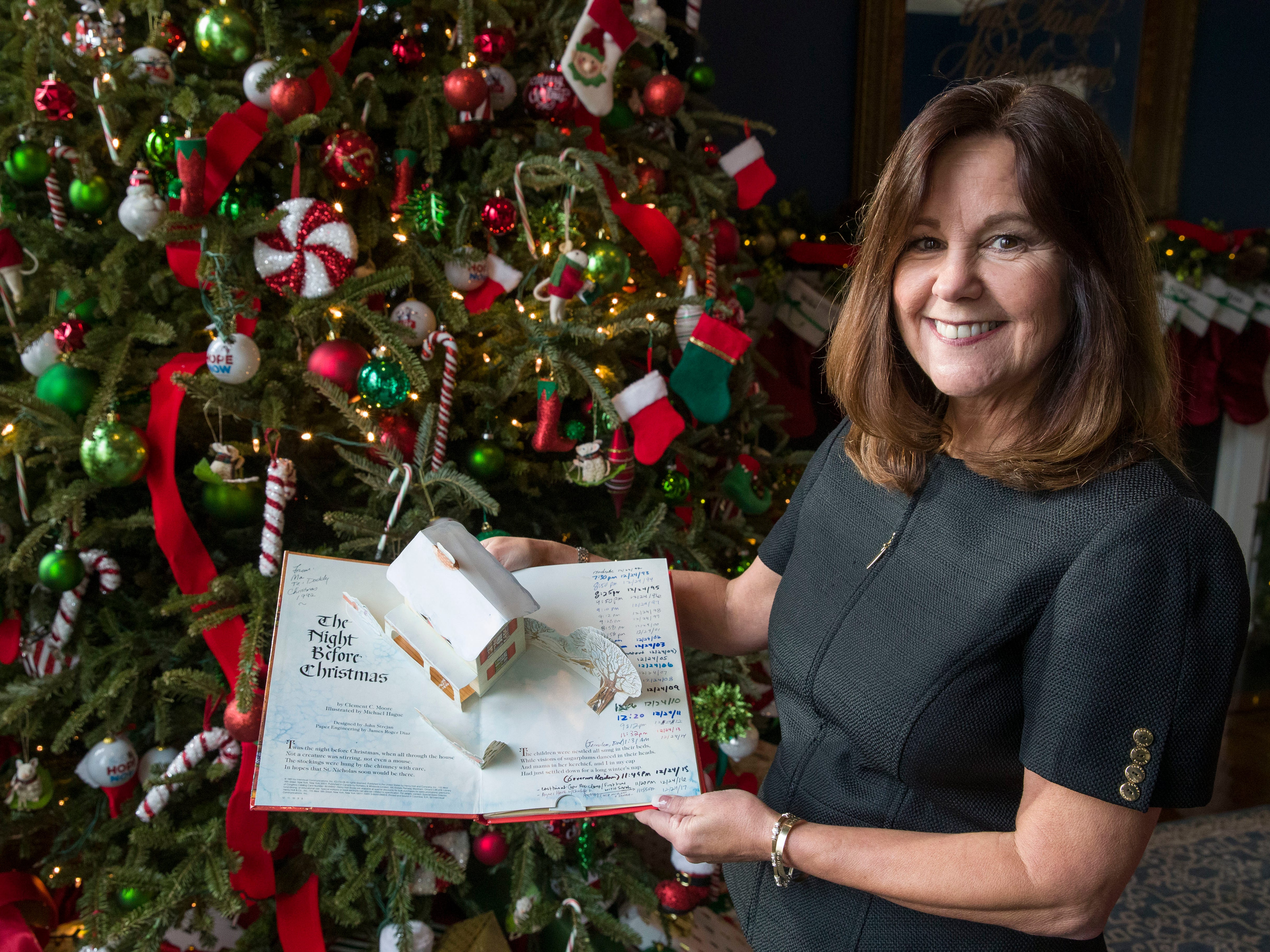 "Karen Pence poses for a photograph holding the family copy of ""The Night Before Christmas,"" as she gives a tour of the holiday decorations at the Vice President's residence, Thursday, Dec. 6, 2018, in Washington."