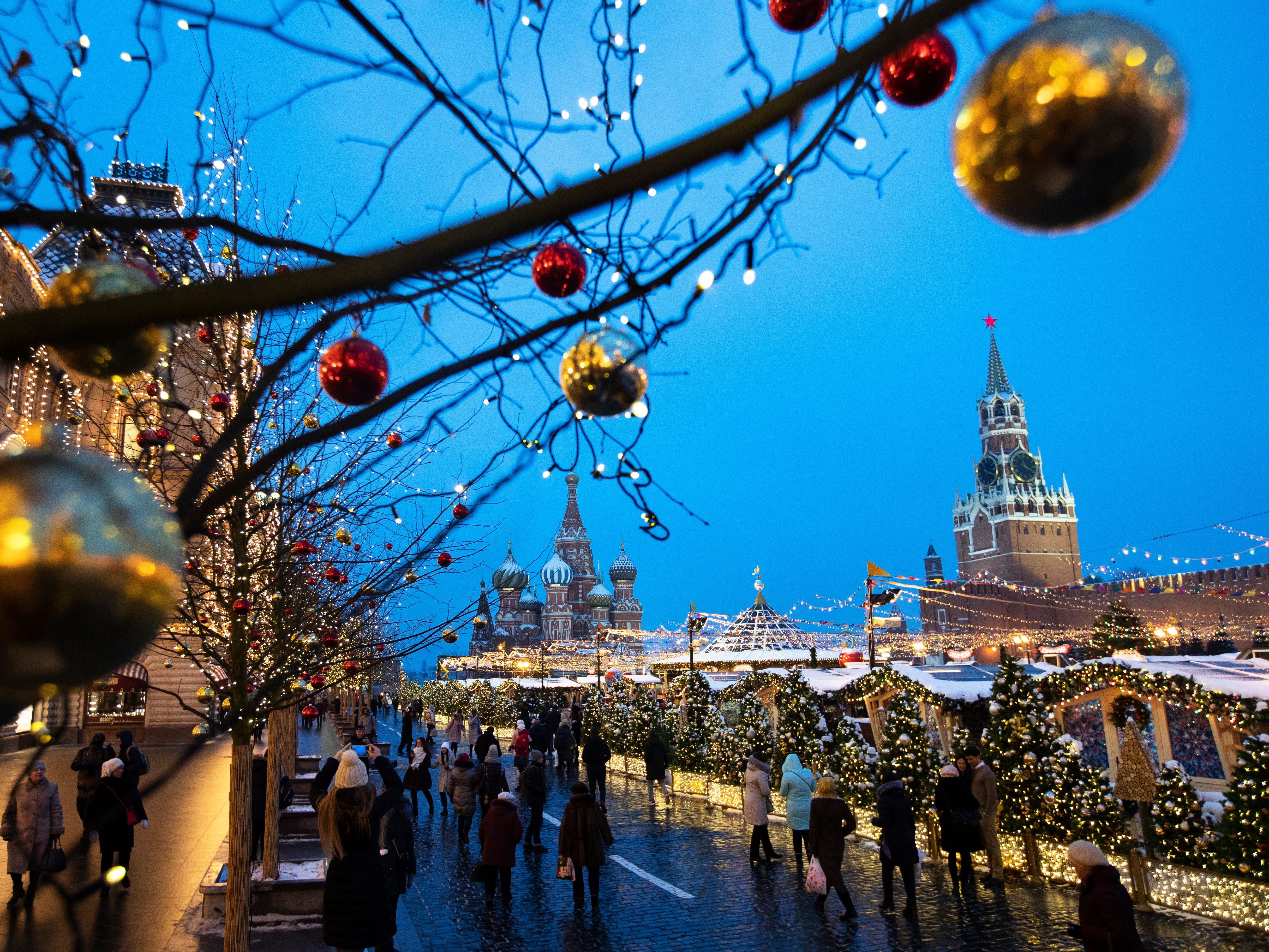 People walk in Red Square decorated for Christmas and New Year celebrations, with the St. Basil's Cathedral, center, and the Kremlin's Spasskaya Tower, right, in the background, in Moscow, Russia, Friday, Dec. 21, 2018.