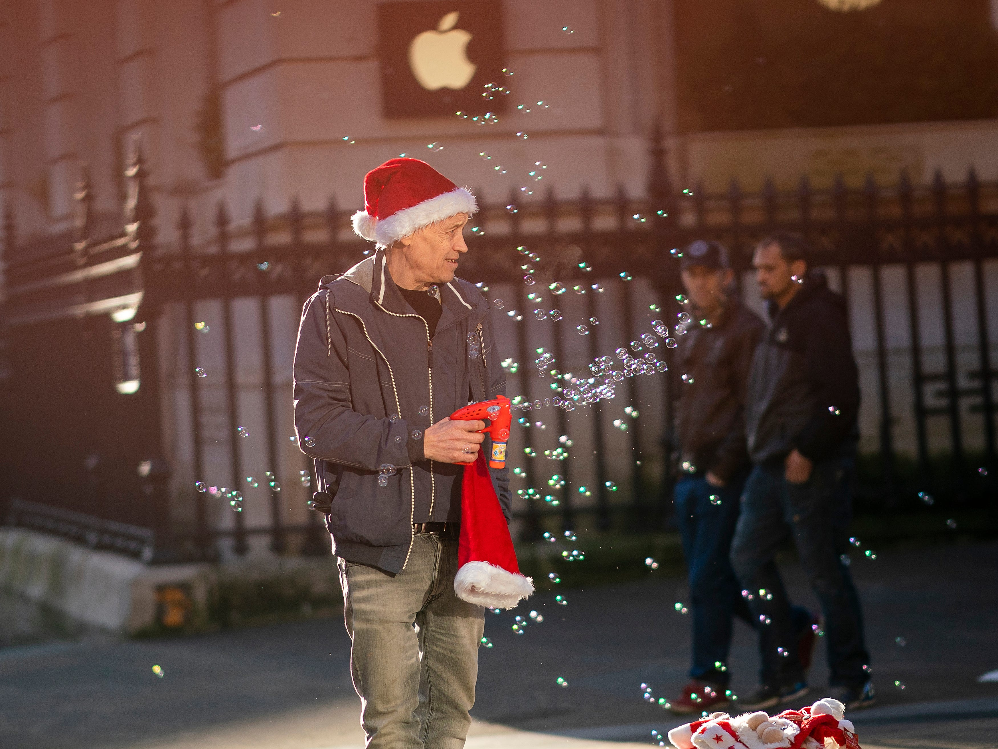 A street vendor sells Santa hats and a bubble machine as shoppers make their last minute purchases on Christmas Eve on December 24, 2018 in Birmingham, England.