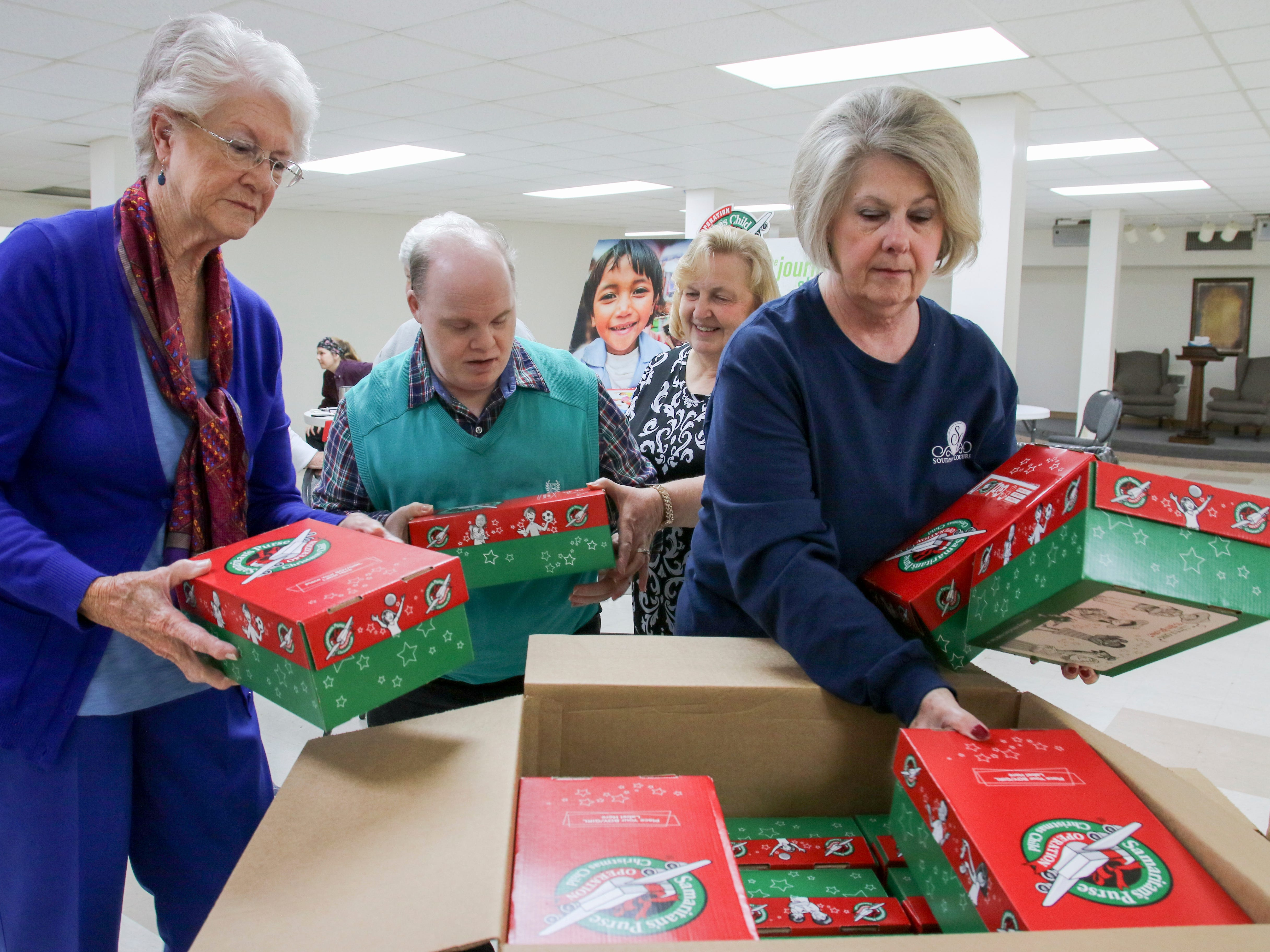 Barbara Parker, left, Wilton Cook, Gladys Cook and Linda Davenport, members of 15th Avenue Baptist Church in Meridian, Miss., place shoebox gifts for children overseas into boxes Monday, Nov, 19, 2018, to be delivered during Operation Christmas Child, a project of Samaritan's Purse International Relief. The church collected 6,500 shoeboxes to go with the amount collected by other churches throughout the area.