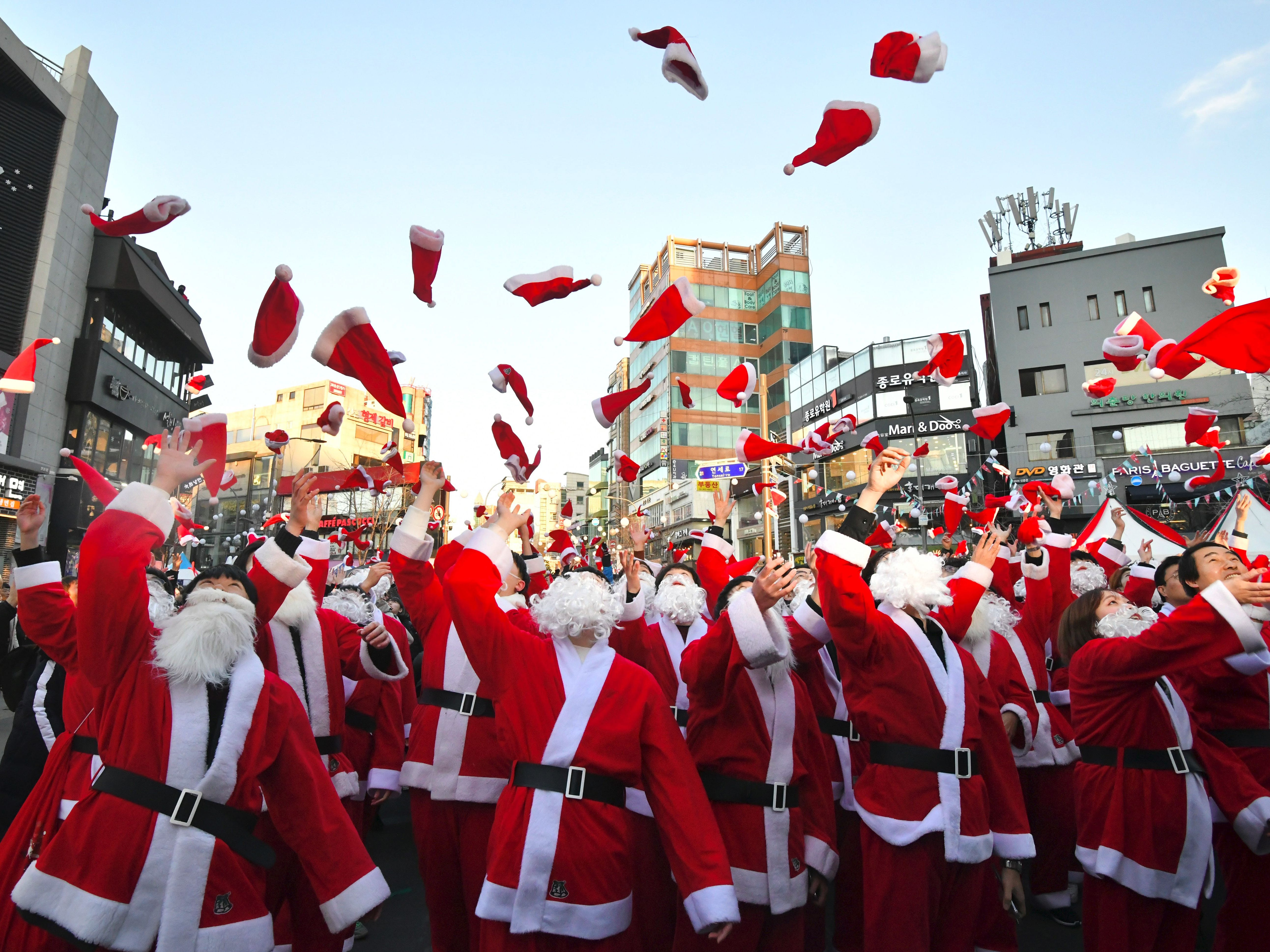 South Korean volunteers in Santa Claus outfits throw Santa hats during a ceremony before the delivery of Christmas gifts in Seoul on December 24, 2018. - The volunteers will deliver Christmas gifts to 1,200 kids from 800 poor families in Seoul on Christmas eve.