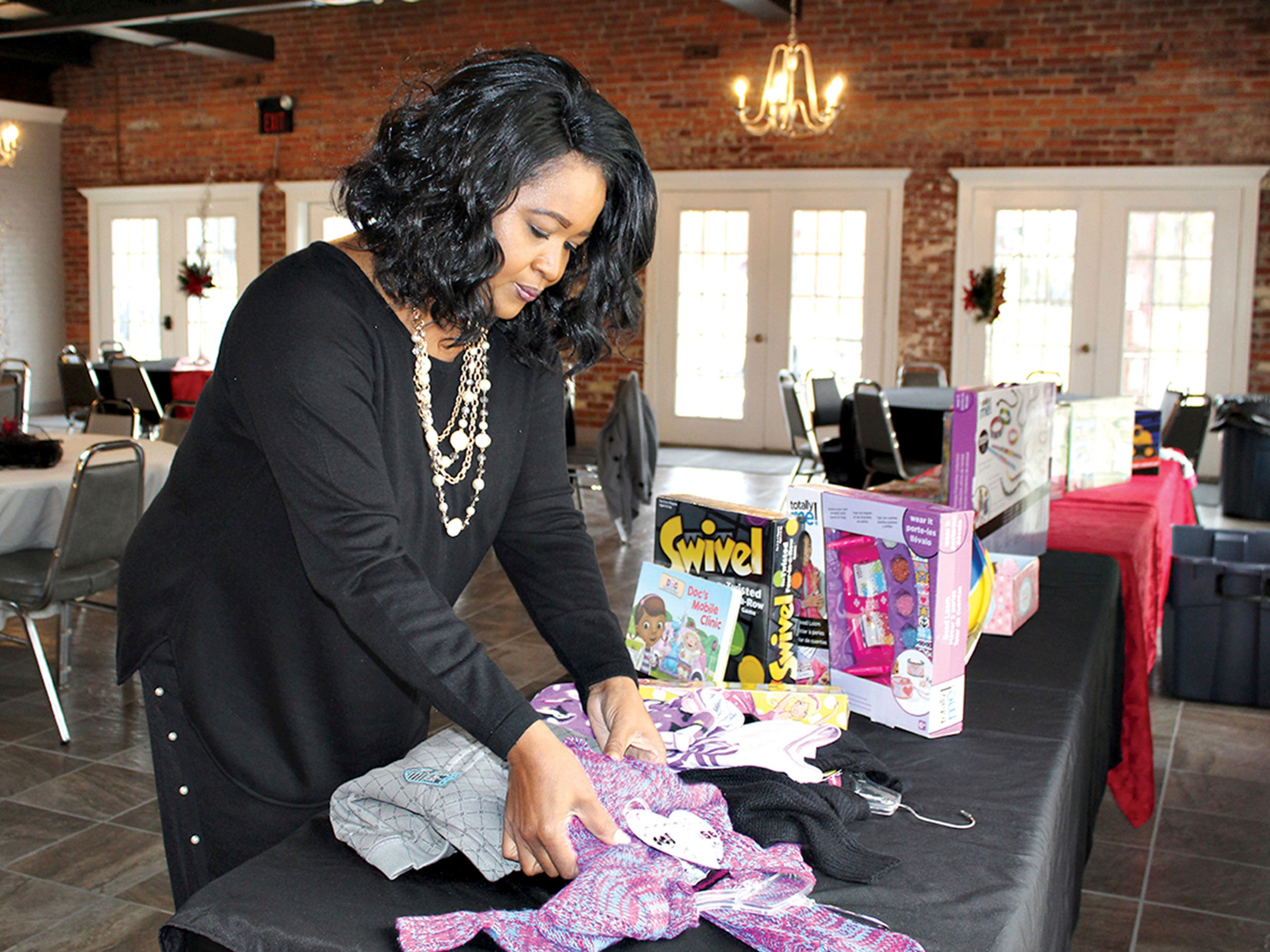 In this Dec. 7, 2018 photo, Glenda Buckhalter, director of community outreach for the city of Columbus, Miss., prepares toys and clothing for children at Regal Hall.