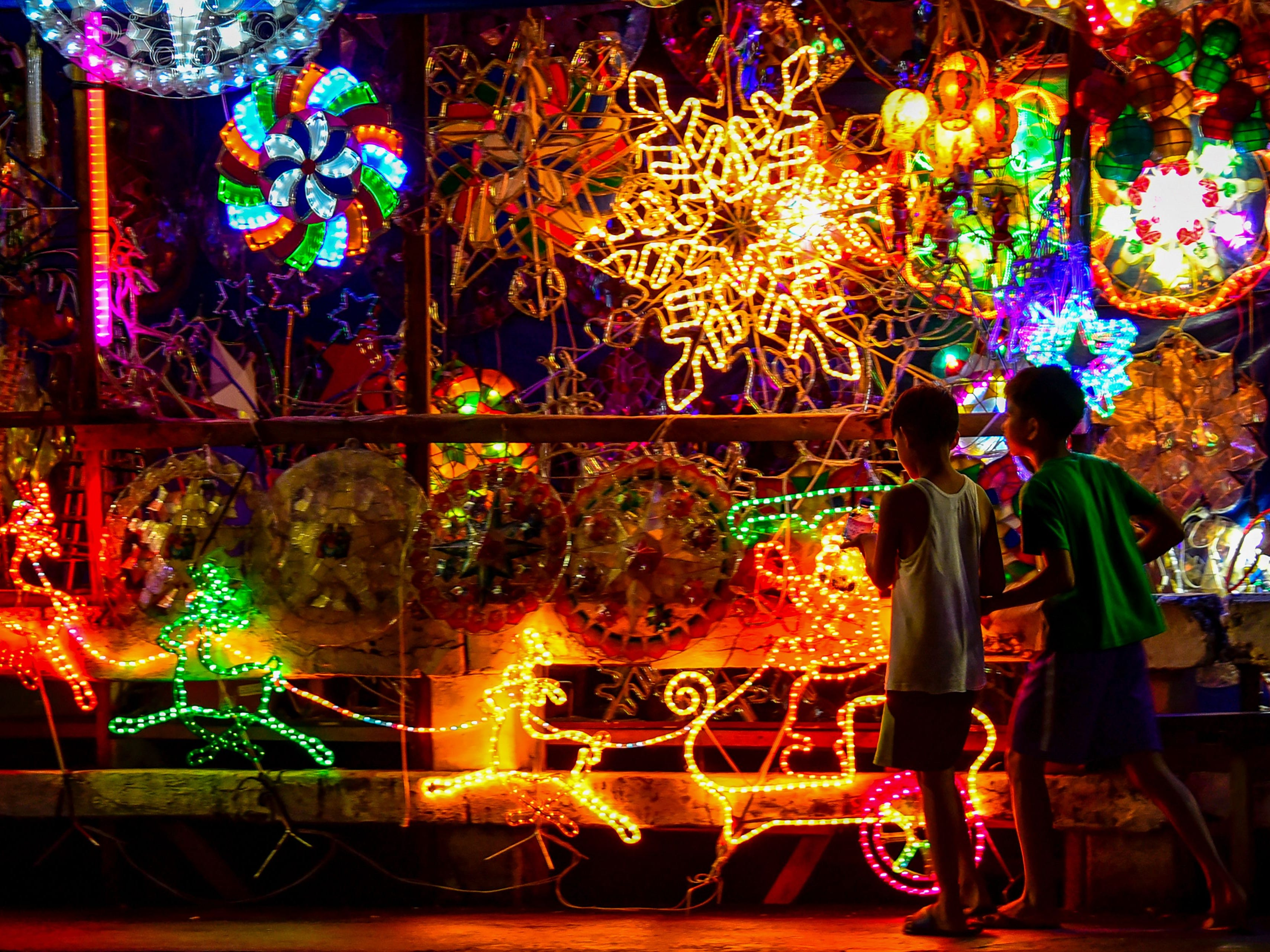 Children walk past Christmas lanterns known locally as 'parol' on display along a street in Manila on December 24, 2018. - Parol are star-shaped Christmas lanterns patterned to resemble the Star of Bethlehem, and are made from bamboo covered with paper. They are displayed in houses, offices, buildings, and streets, and according to Filipino tradition and beliefs, also represent the victory of light over darkness.