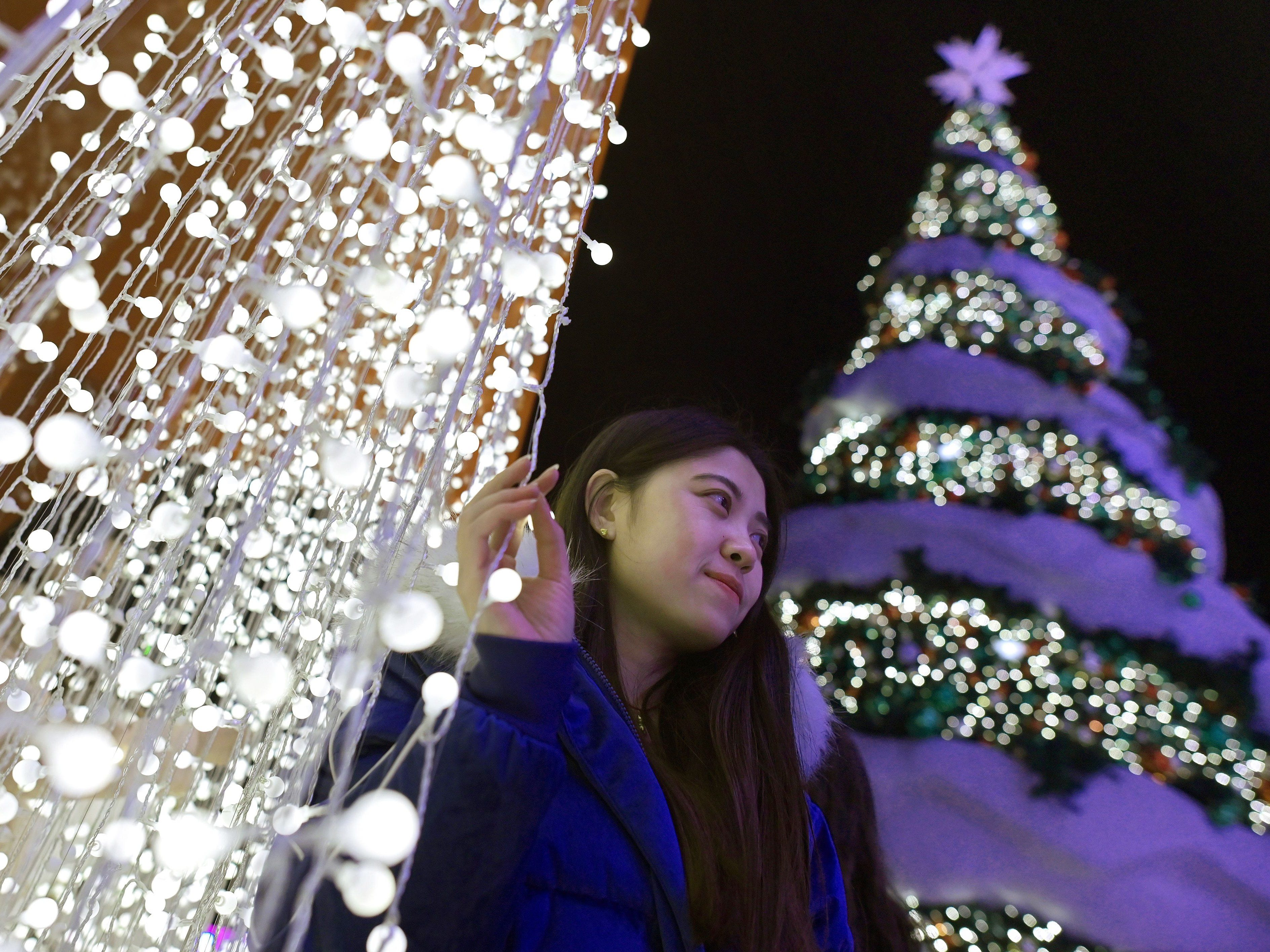 A woman poses for a photograph next to a Christmas tree at a shopping mall in Beijing on December 22, 2018.