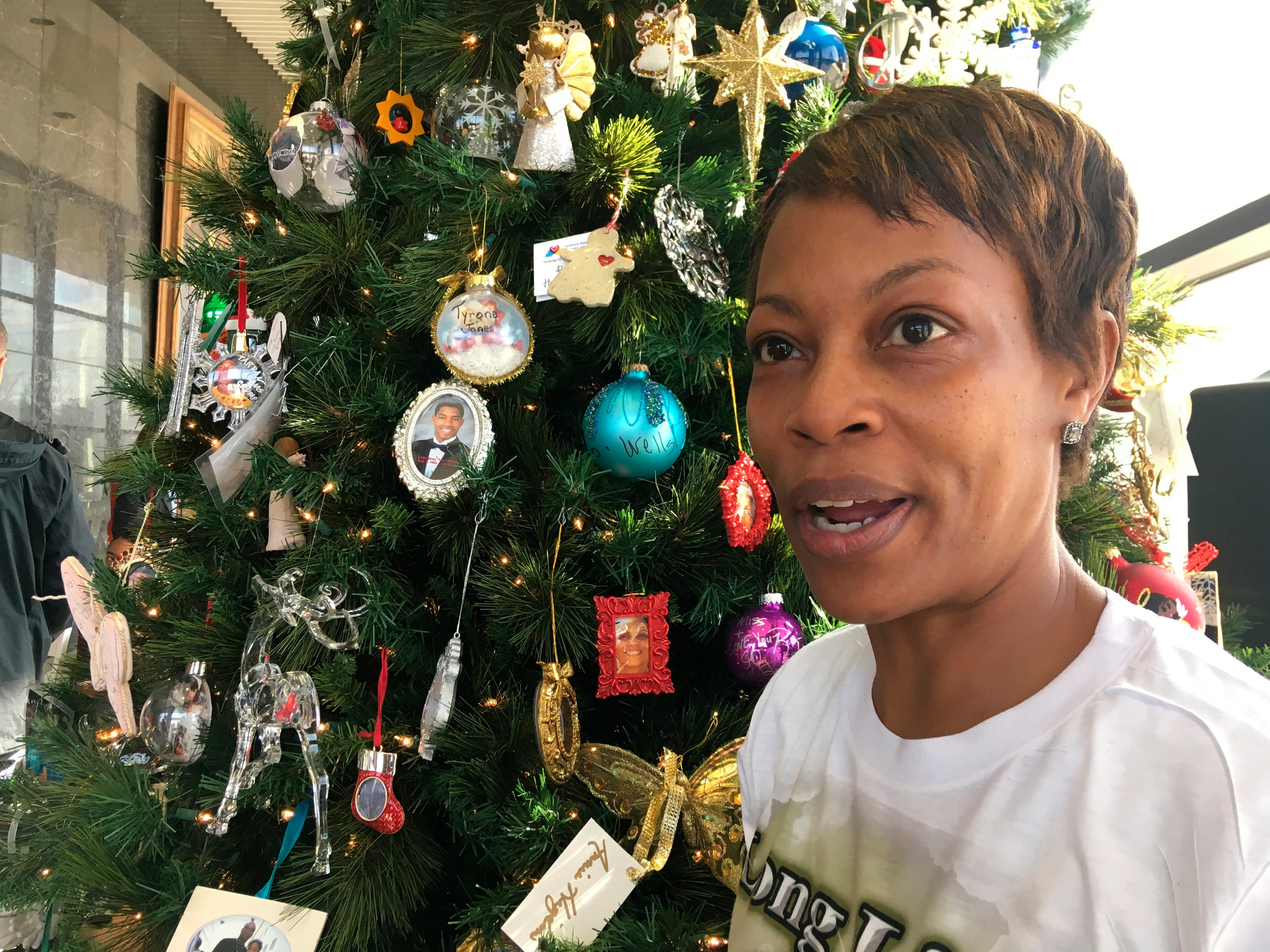 Lisa Donegan speaks in an interview after a tree-lighting ceremony in Jackson, Miss., Tuesday, Dec. 18, 2018. A Christmas tree in the Mississippi government building has been decorated to honor crime victims. The tree holds more than 600 ornaments with photos of crime victims including her son.