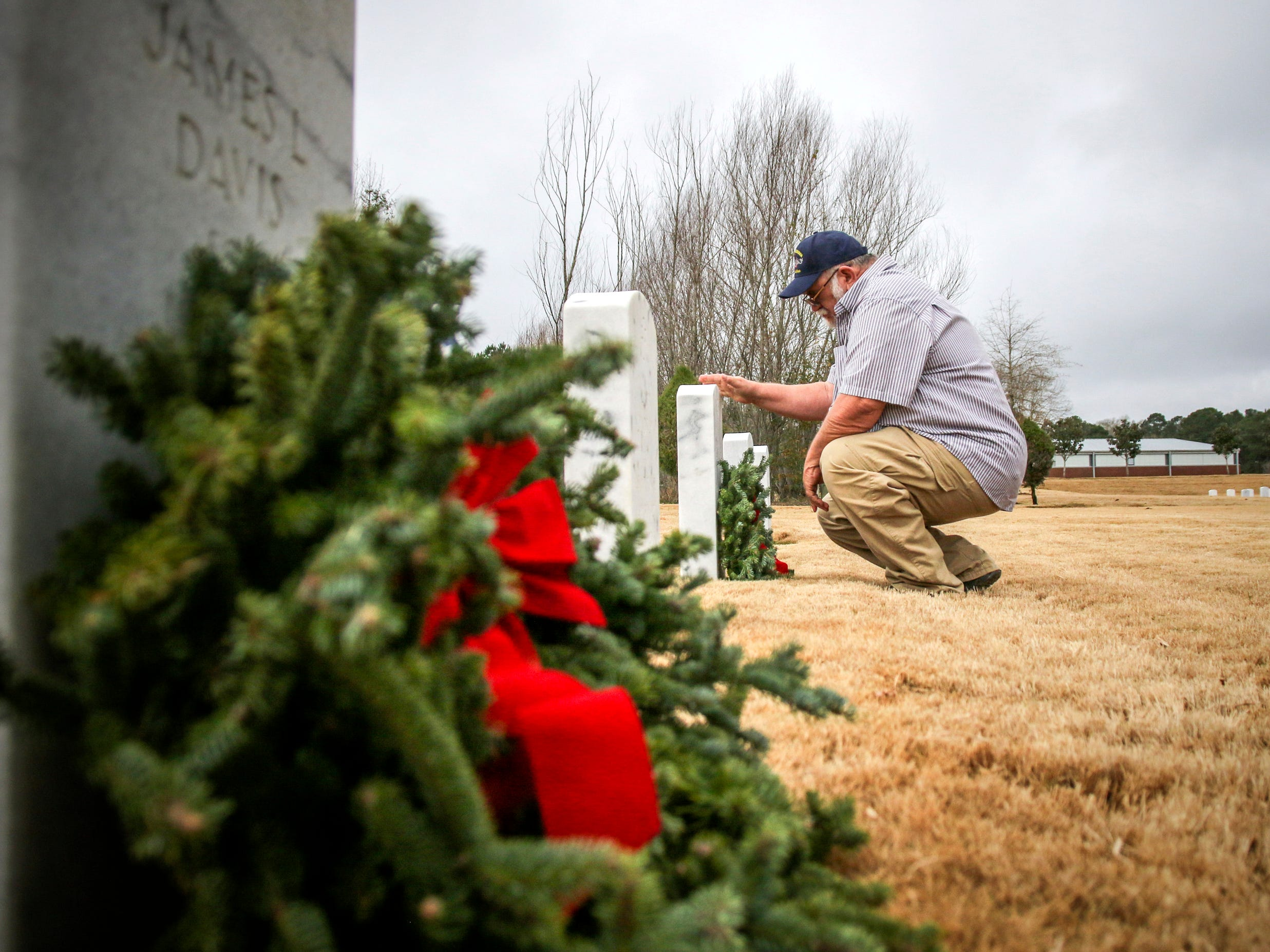 John Gamber kneels next to his son Bryan's gravesite after laying a wreath during the 8th annual Wreaths Across America campaign at Mississippi Veterans Memorial Cemetery in Newton, Miss., Saturday, Dec. 15, 2018.