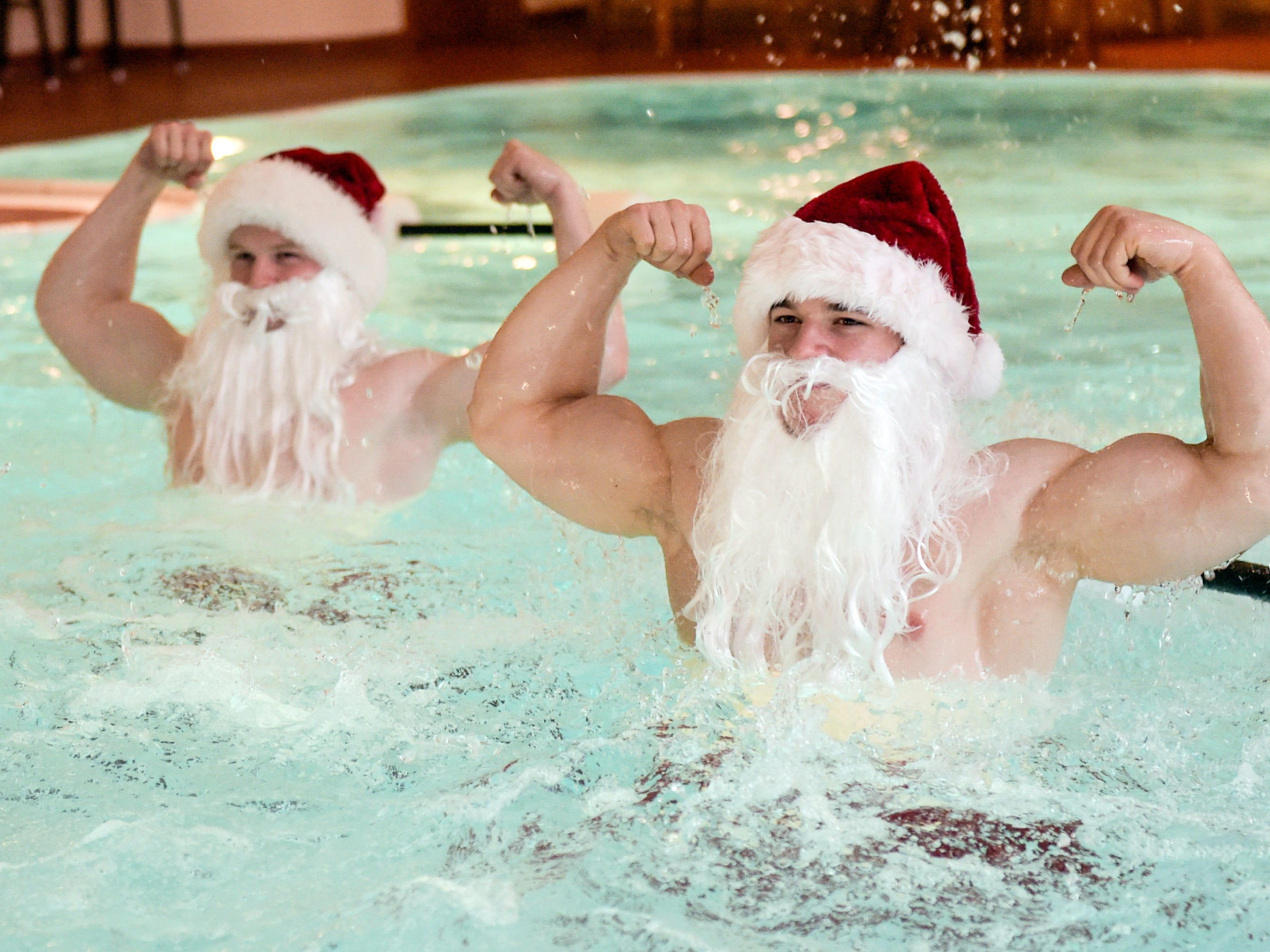 Fitness coaches dressed as Santa Claus pose while doing aqua aeorobics in a pool of the Meridian Spa in Hamburg, northern Germany, during a charity event on December 18, 2018.