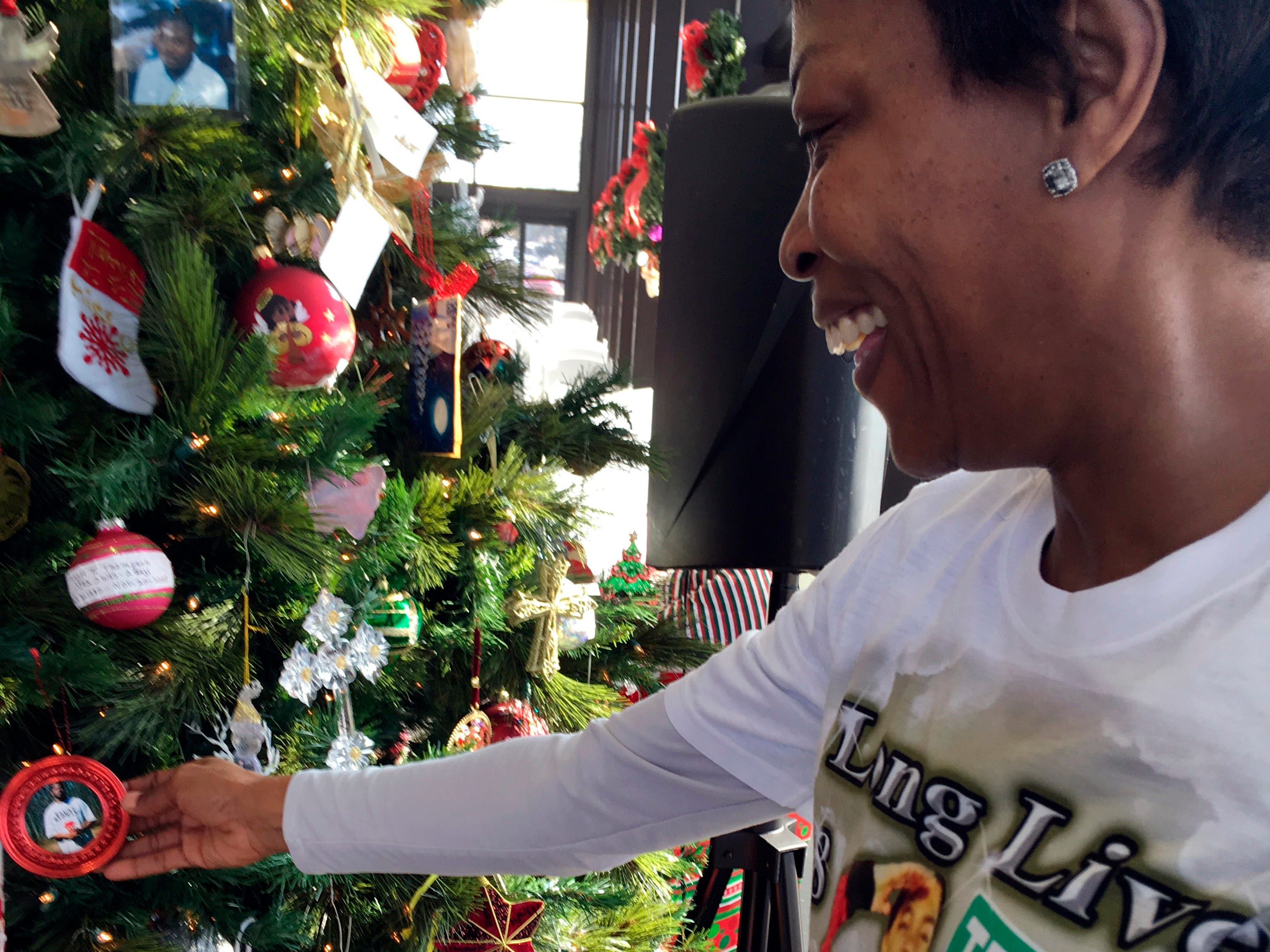 Lisa Donegan of Arlington, Texas, shows an ornament with a photo of her son, 21-year-old Tray Williams, on a Christmas tree honoring Mississippi crime victims, Tuesday, Dec. 18, 2018, in Jackson, Miss.