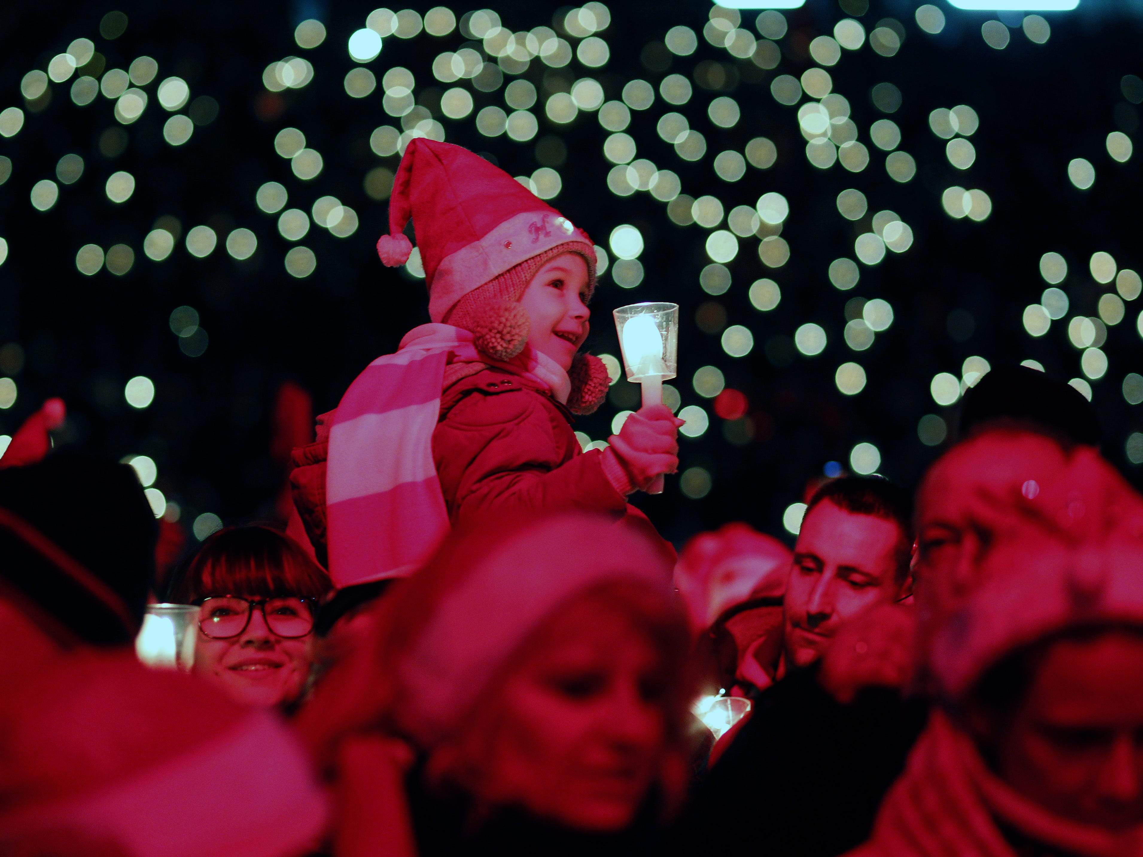 Tarja, age 4, daughter of a fan family of the FC Union football club, which permitted she to be photographed, hold a candle as she sing Christmas carols in the club's stadium  on December 23, 2018 in Berlin, Germany. The annual gathering has become a firm tradition now in its 16th year. All 28,500 tickets were sold.