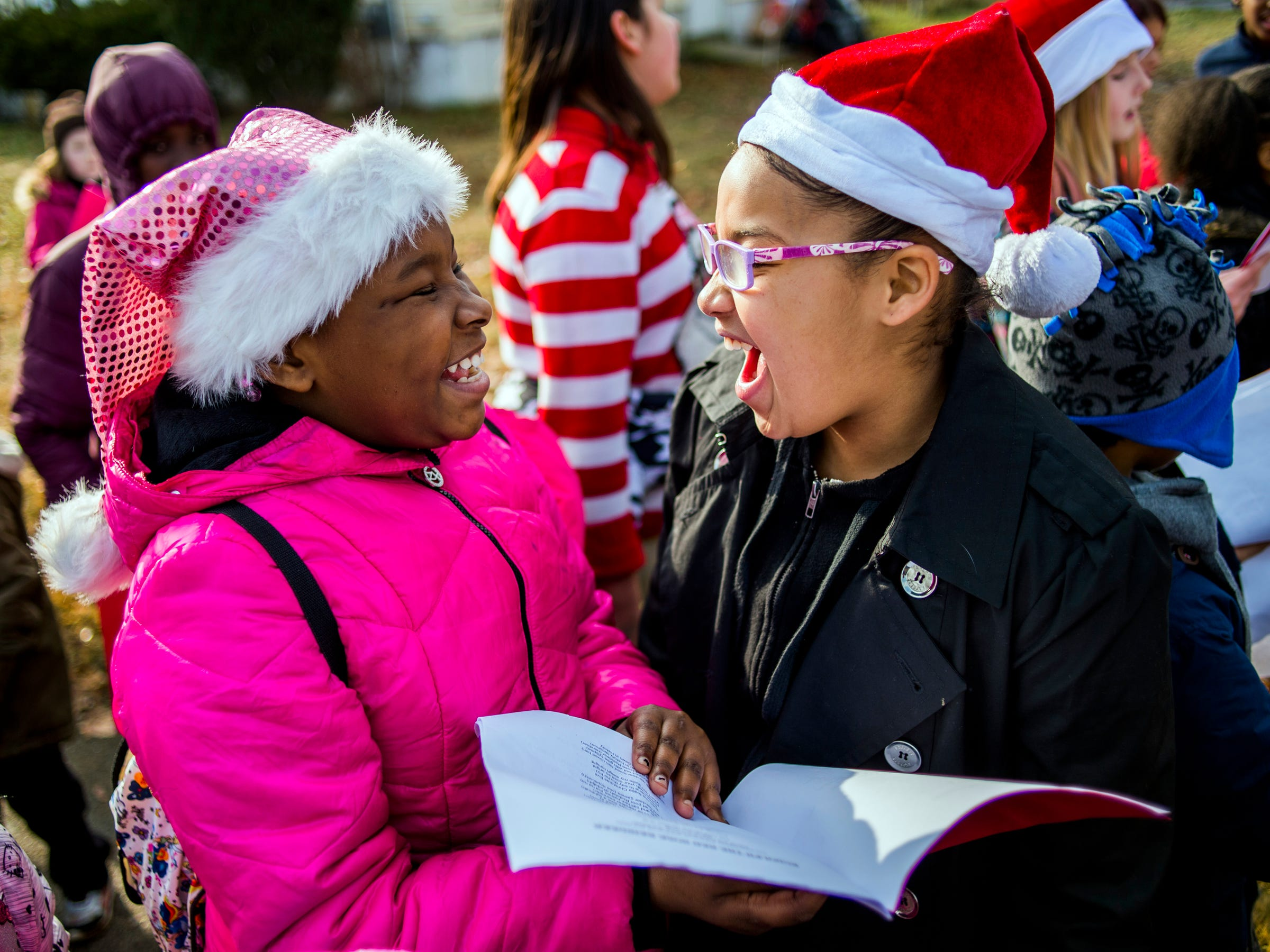 "Fourth-graders and best friends Leanisha Person, left, and Amira Wickham, both 9, smile as they sing out the lyrics to ""Rudolph the Red-Nosed Reindeer"" alongside hundreds of Freeman Elementary School students serenade the school's surrounding neighborhood with Christmas carols on Thursday, Dec. 13, 2018 on the south side of Flint, Mich"
