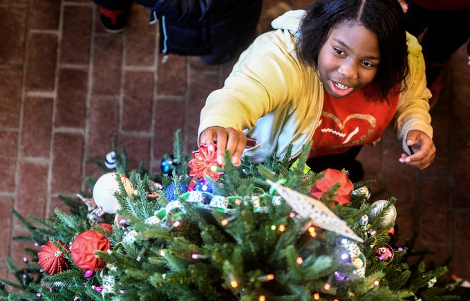 Katie McLeod hangs an ornament as the Boys & Girls Club decorates the tree at the Lafayette County and Oxford Public Library, in Oxford, Miss. on Tuesday, December 4, 2018.