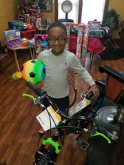 Zachariah Bills, 5, won a bike at the Futurlistic Barber and Beauty Salon annual toy drive in addition to getting other toys. Each child's name was place in a drawing for the bike.