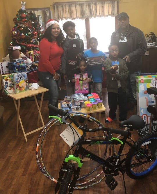 Nikita Jones, a hairstylist at Futurlistic Barber and Beauty Salon, and Robert Murphy, the owner, stand with children at the shop's annual toy drive on Christmas Eve. Children (left to right) are Marion Brown, Laniah  Farley, Montrail Brown and Zachariah Bills.