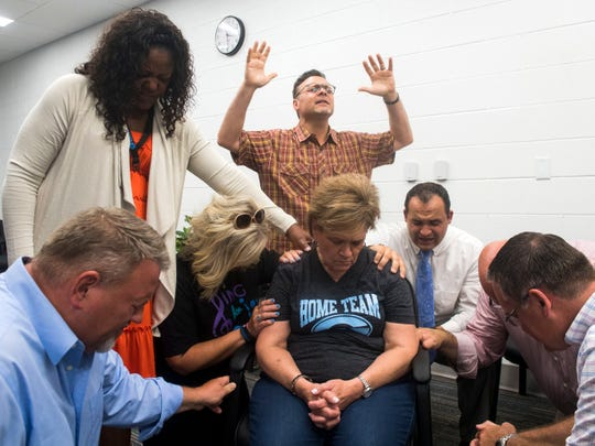 Church and community leaders lay hands on Gibbs Middle School Principal Cindy White during a community prayer walk at the new middle school on Aug. 5, 2018.