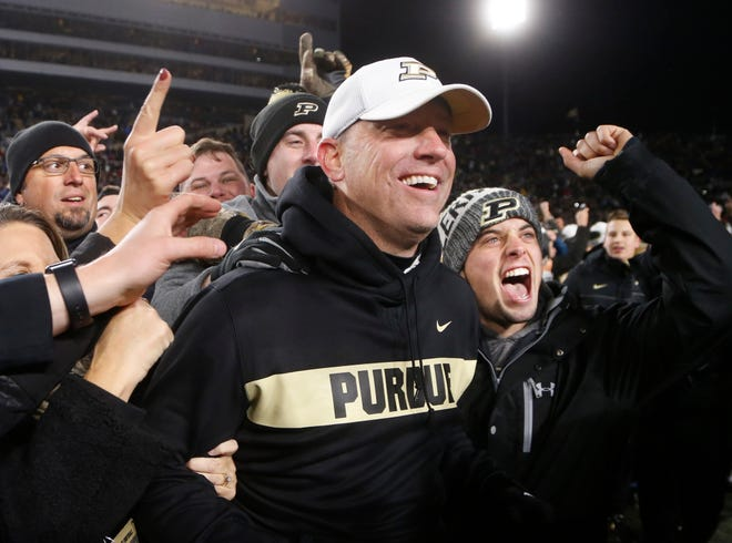 Head coach Jeff Brohm is mobbed by the Purdue faithful after the Boilermakers upset No. 2 ranked Ohio State 49-20 Saturday, October 20, 2018, at Ross-Ade Stadium.