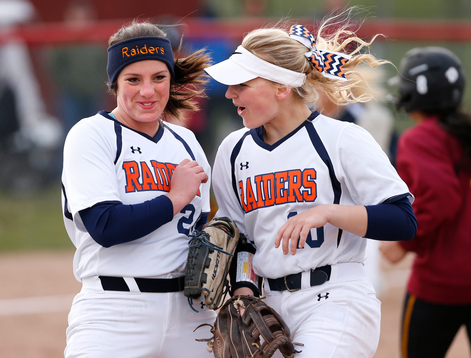 Harrison pitcher Jillian Mathis, left, celebrates with Olivia Stansbury after striking out Britney Butcher of McCutcheon with the bases loaded for the final out in the bottom of the fourth inning Tuesday, April 10, 2018, at McCutcheon High School. Harrison defeated county rival McCutcheon 7-5.