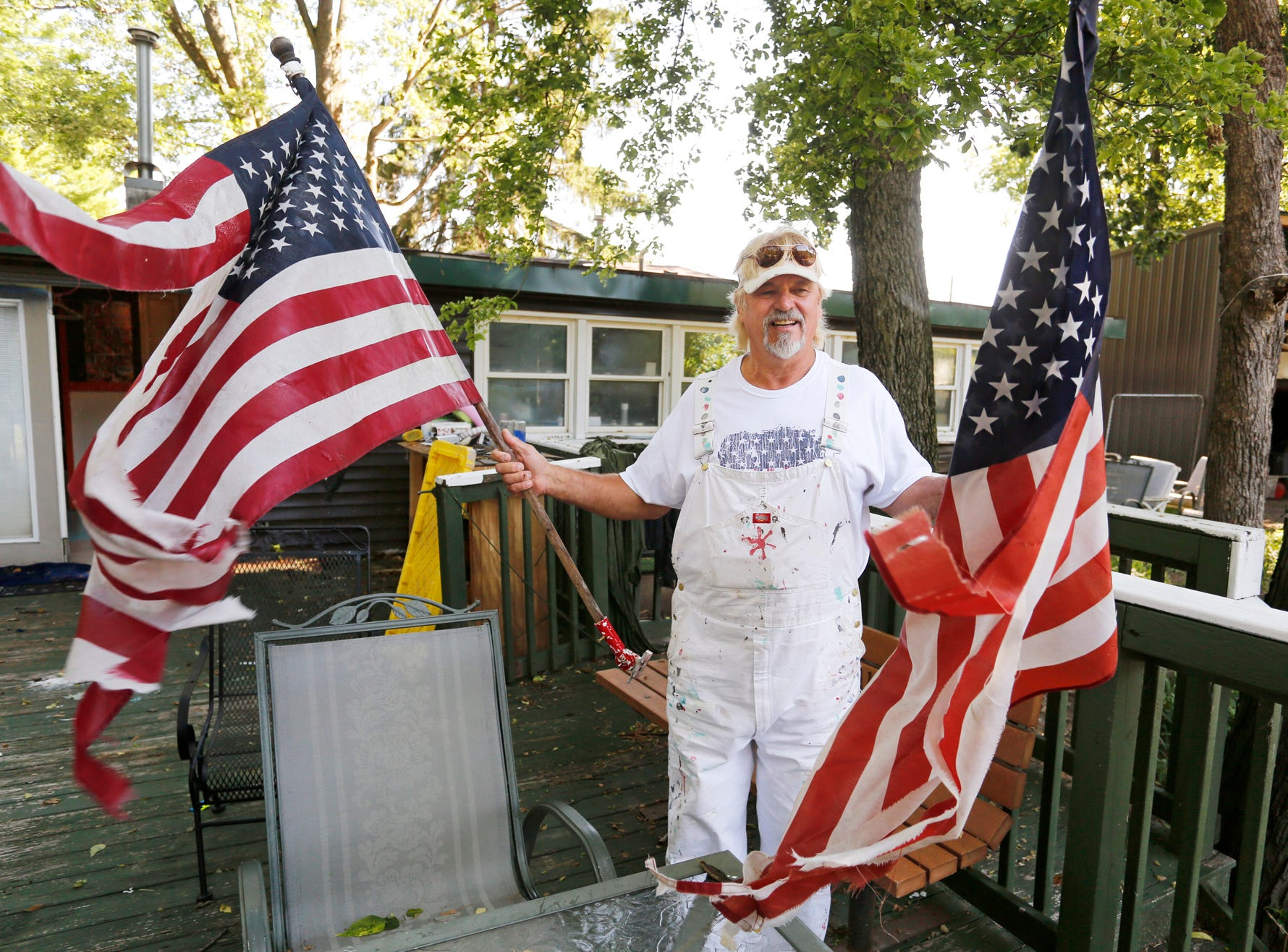 "Jeff Seramur gathers two US flags that are worn and faded from his back deck Friday, July 6, 2018, at his home on Horseshoe Bend. Seramur's home on the Tippecanoe River was flooded last February. It was the fourth time his home has been flooded. ""They (flags) made it through the flood, now it's time to retire them,"" said Seramur."