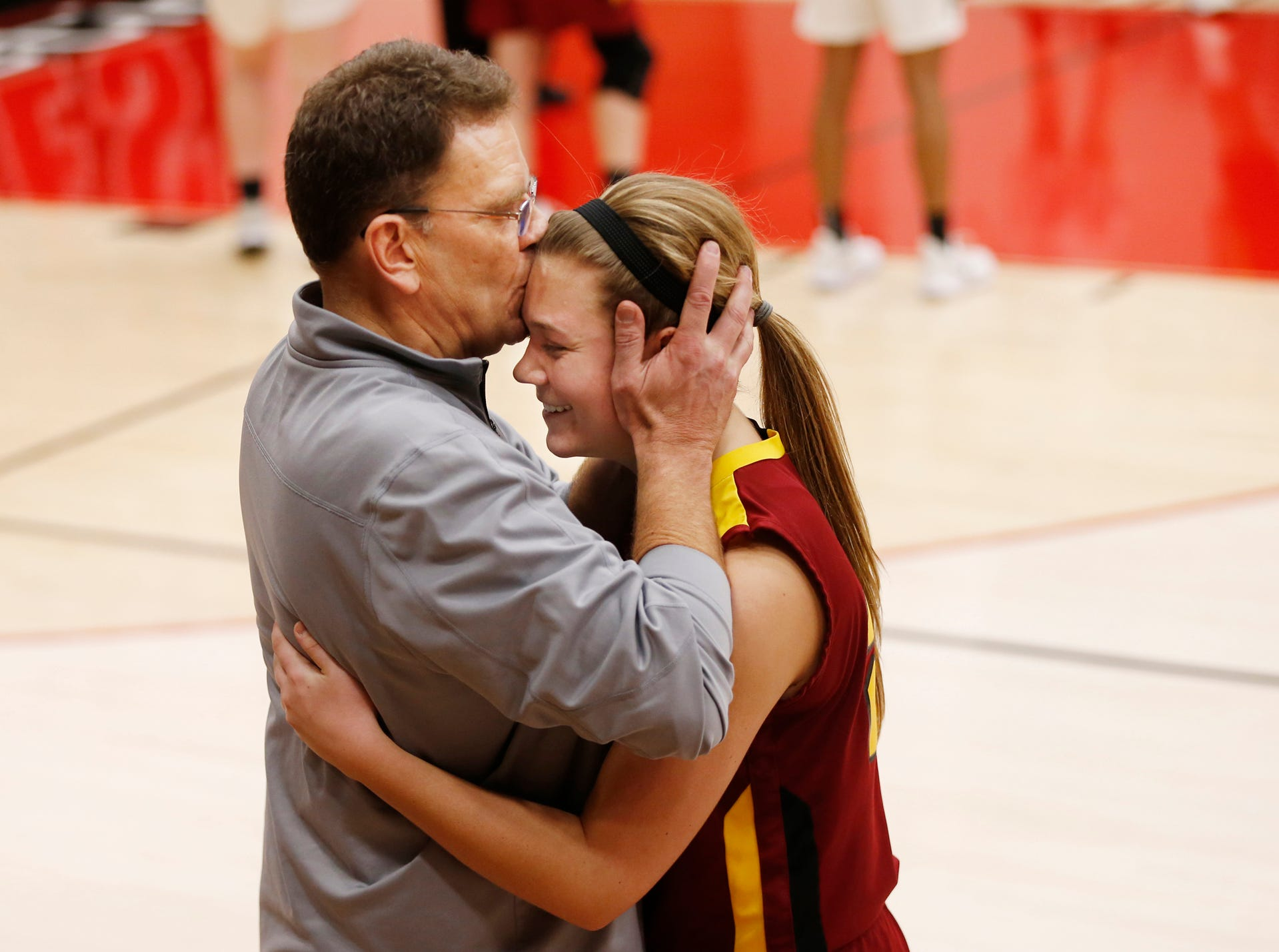 McCutcheon head coach Jeff Knoy gives his daughter Anabelle a kiss as she comes out of the game late against Zionsville in the girls basketball sectional Tuesday, January 30, 2018, at Logansport. It was the final game as a Maverick for Anabelle Knoy. Zionsville defeated McCutcheon 71-32.