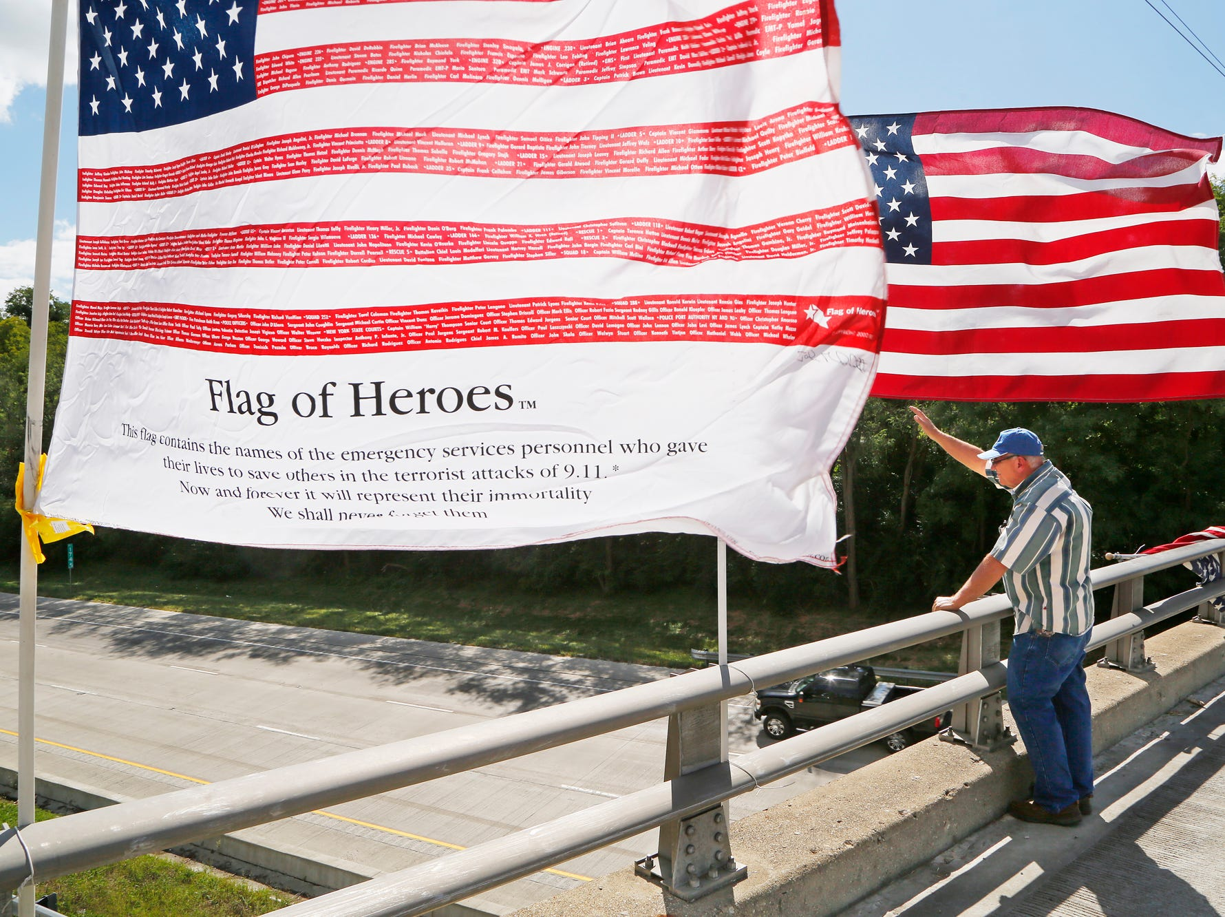 "Robert McKinniss waves to motorists and truckers on Interstate 65 as they honk their horns while passing beneath his collection of flags Tuesday, September 11, 2018, on the County Road 200 N overpass near Lafayette. Since the 10th anniversary of the September 11 terrorists attacks, McKinniss has posted flags on the bridge in honor of those who made the ultimate sacrifice that day. ""I want people to remember that there are people that care about people, people that put themselves on the line everyday so we can have safety in our lives,"" McKinniss said."