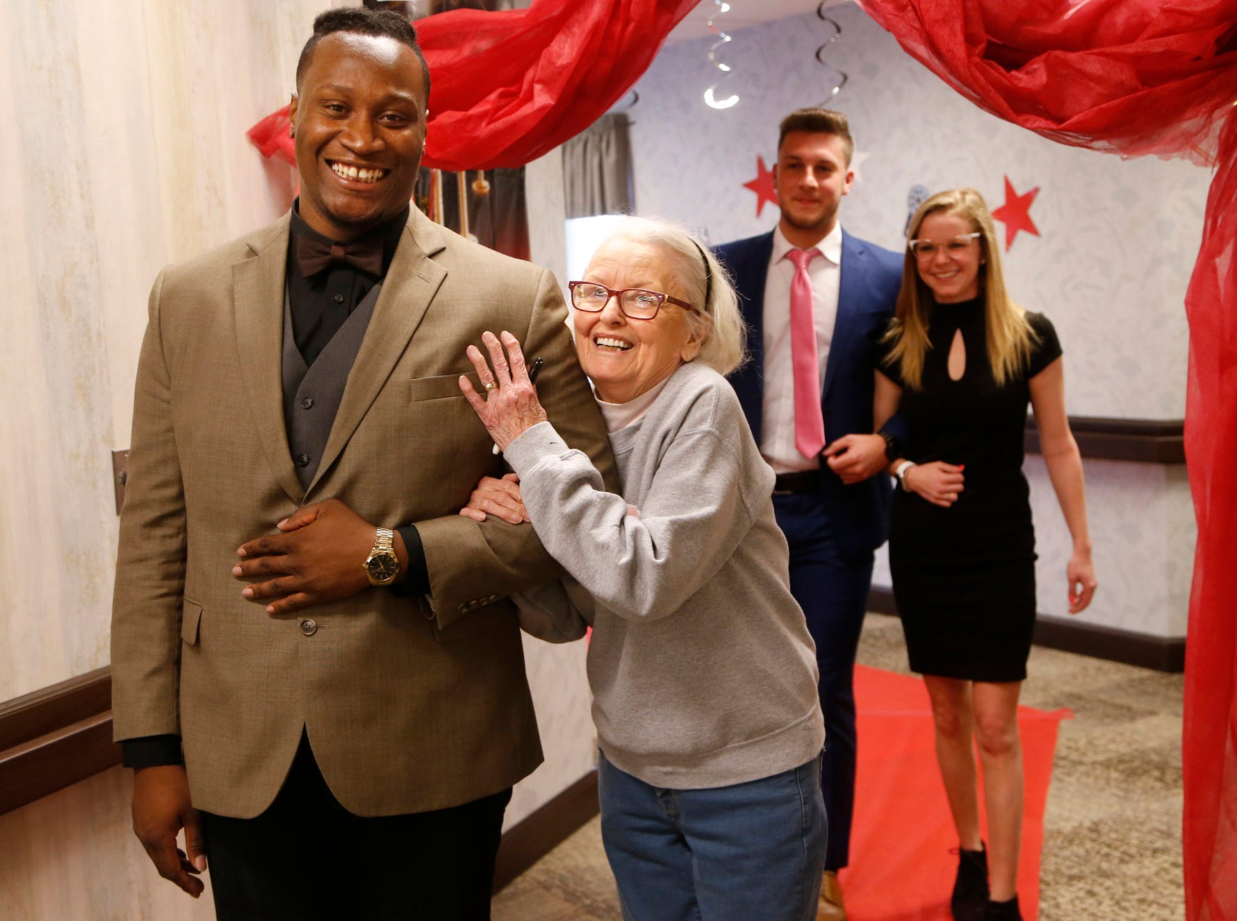 Mary Ezra beams as she is escorted to the Senior Prom by Purdue senior defensive tackle Keiwan Jones Tuesday, March 20, 2018, at Aster Place, 741 Park East Boulevard in Lafayette. Several members of the Purdue football team joined in the festivities that culminated with Ruth Potter named Queen and Paul Jansen King of the Senior Prom.
